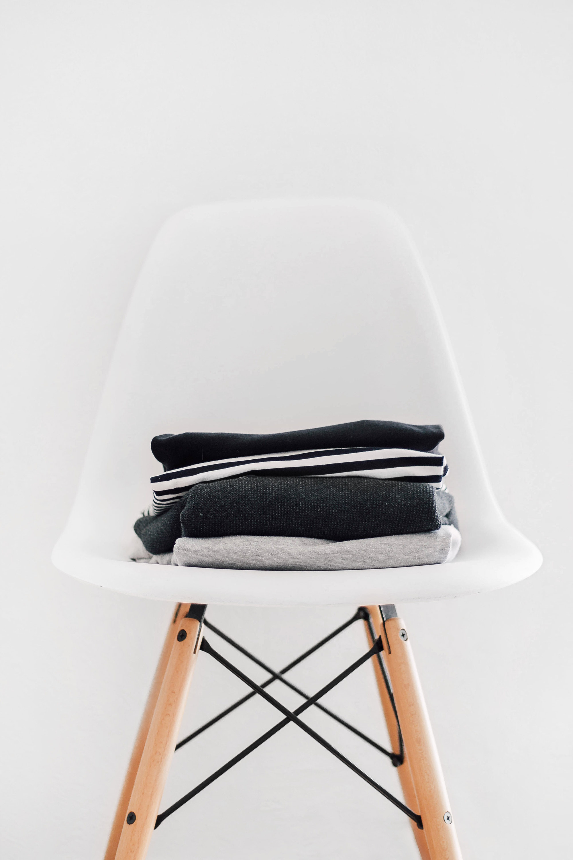 4-pile-of-sweaters-on-white-eames-chair.jpg