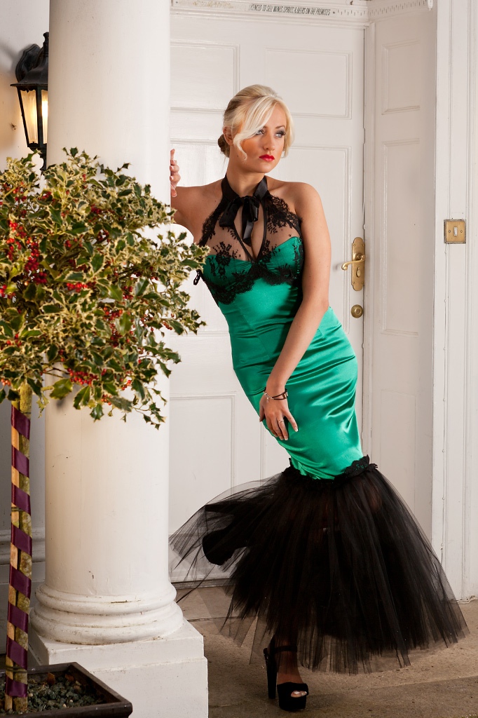 Fashion model posed against pillar in doorway wearing elegant evening dress. Photography by Keith Mindham