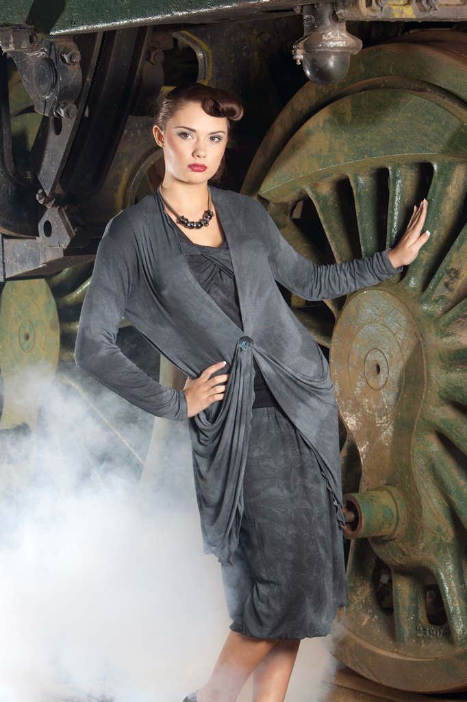 Model posing with giant wheel of steam train, portable lighting used with smoke machine to create steam effect.