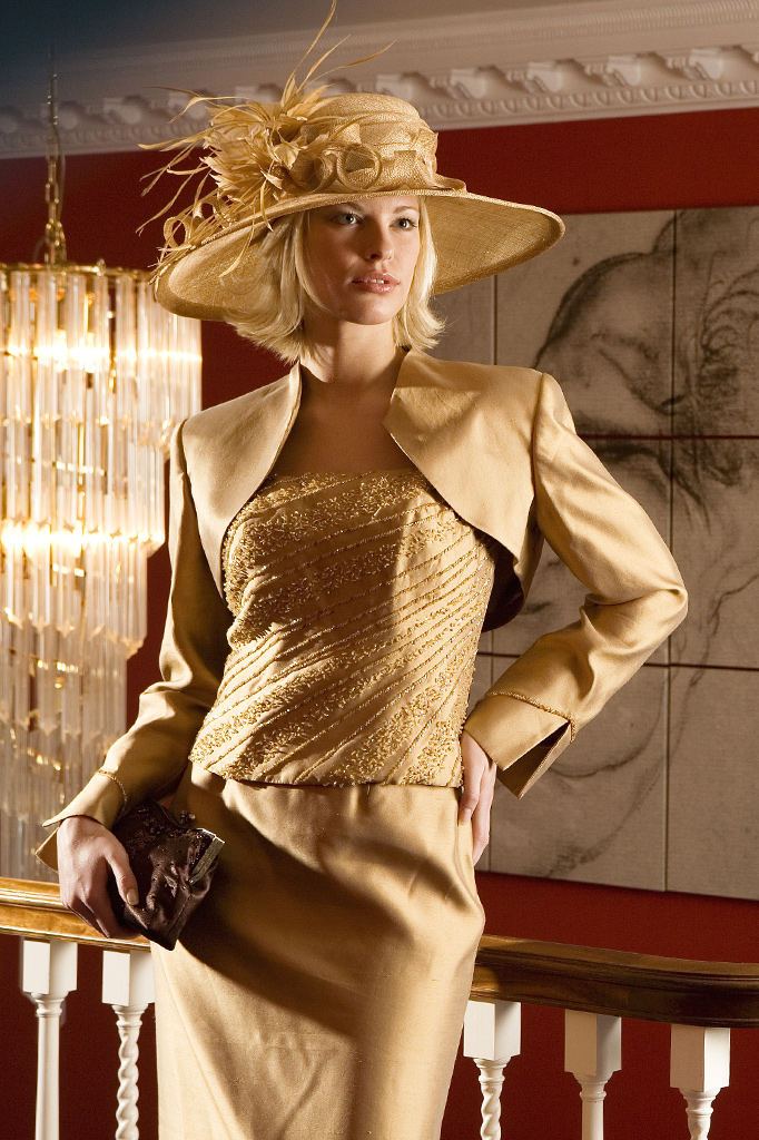 Location fashion photography of female model with gold outfit and hat all lit with strobe lights