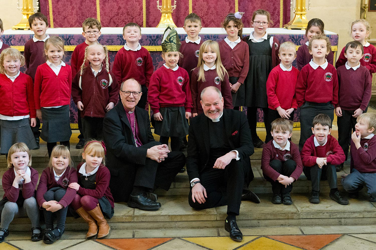 Joe Hawes with Bishop Martin Seeley and school children prior to being installed as  new Dean at St Edmundsbury Cathedral.