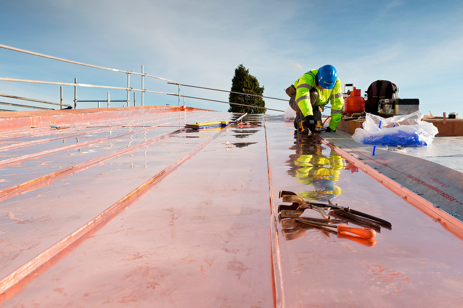 Construction photography of copper roofing being applied to roof at Churchill College, Cambridge.