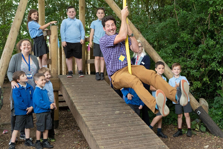 Norfolk Primary School head teacher Pete Dean on the zip wire sponsored by local house builders.