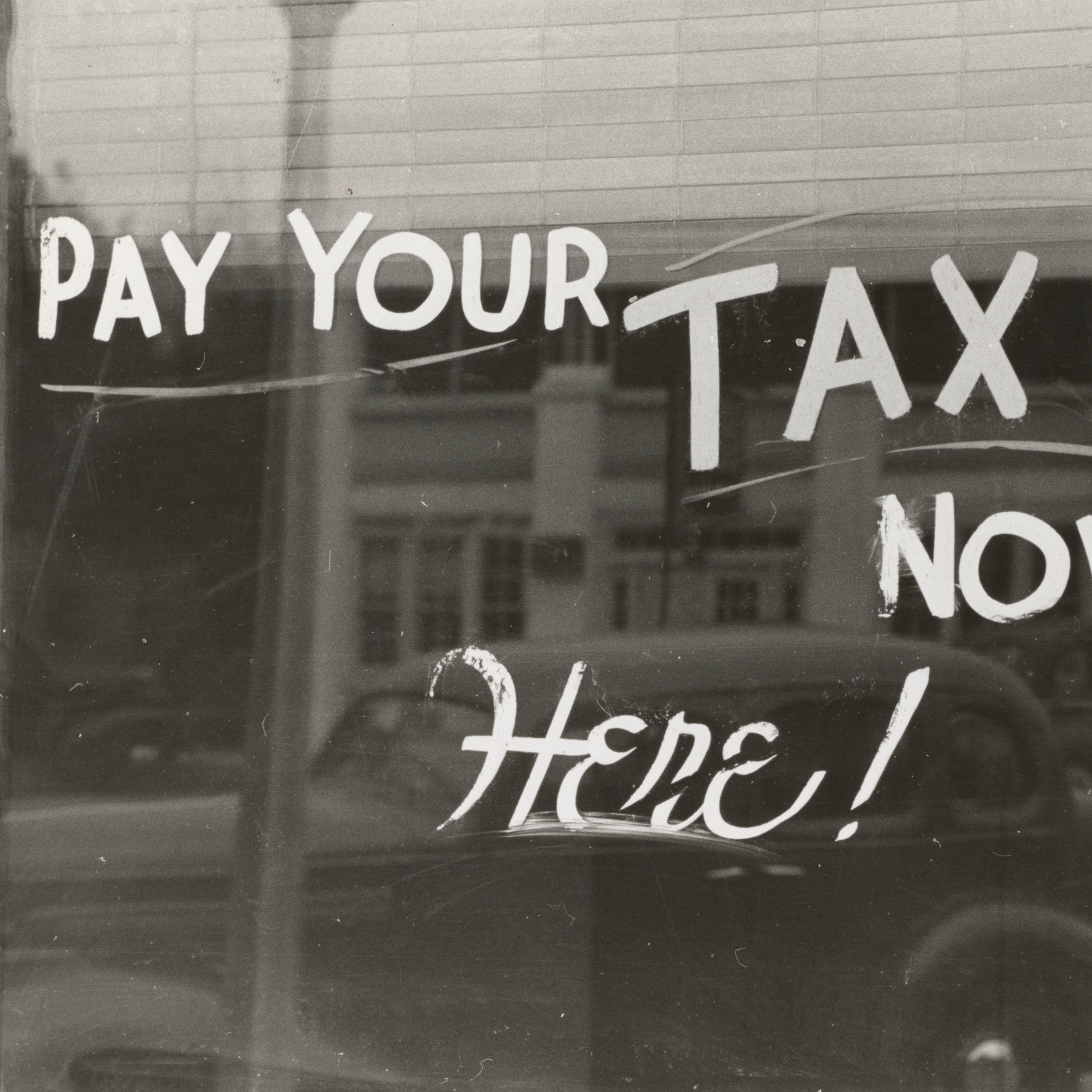 Pay your tax now written on a window