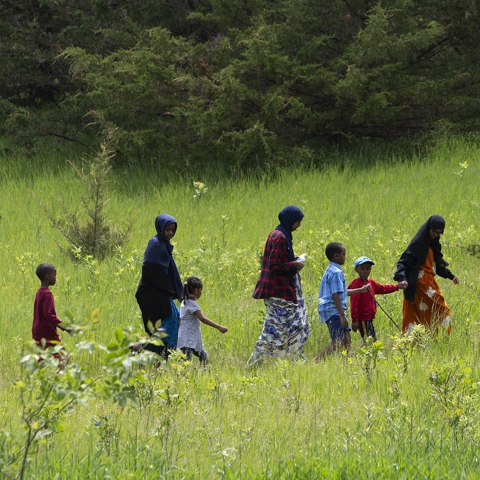 Women and children walking through a field