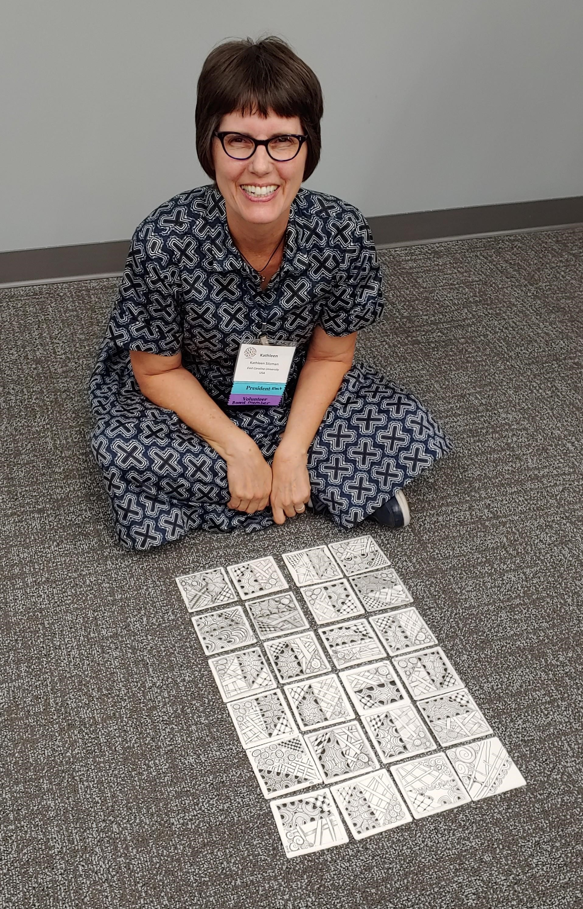 Here is a photo of me at the 2019  International Association for Human Caring Conference in Greenville, South Carolina. I am in the middle of teaching a  Zentangle Class! The tiles have been created by each of my students in the class. They all received the same instructions, but each tile is as unique as the person who created it.  This is a good visual representation of how groups of people process information. They may receive the same input, but as you can see, the output is highly varied. It is important to remember this when teaching and working with all kinds of groups.