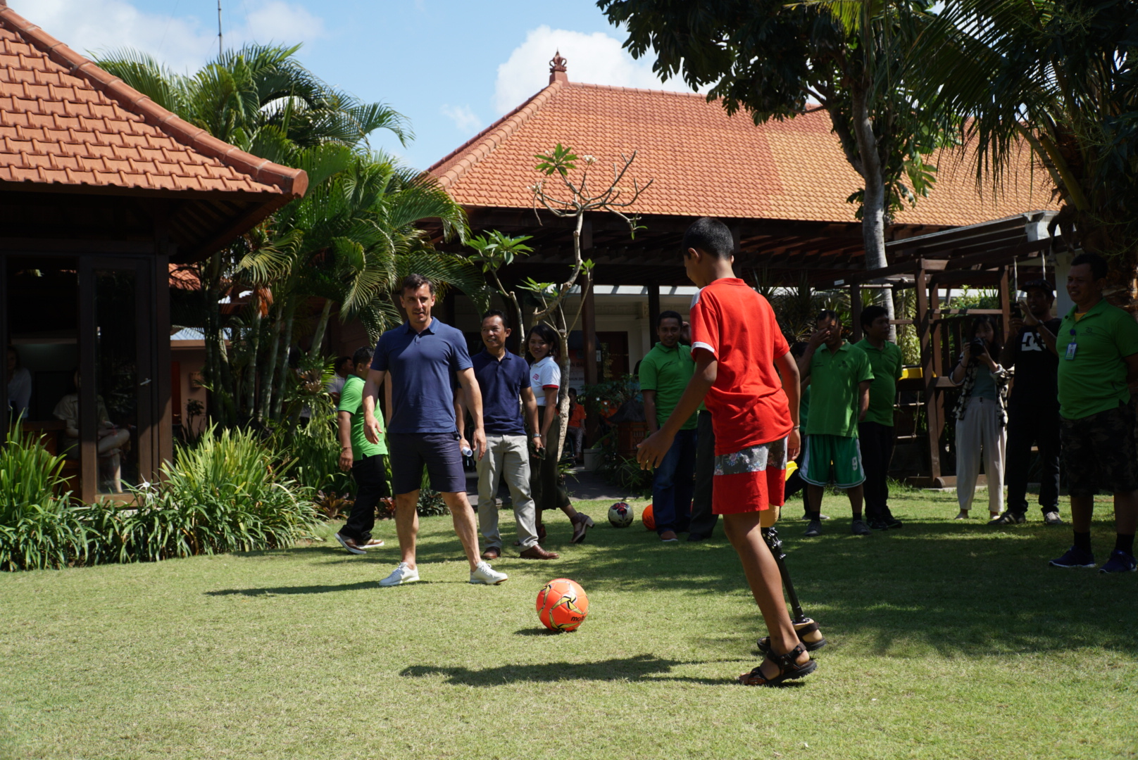Gary Neville playing football with a prosthesis user