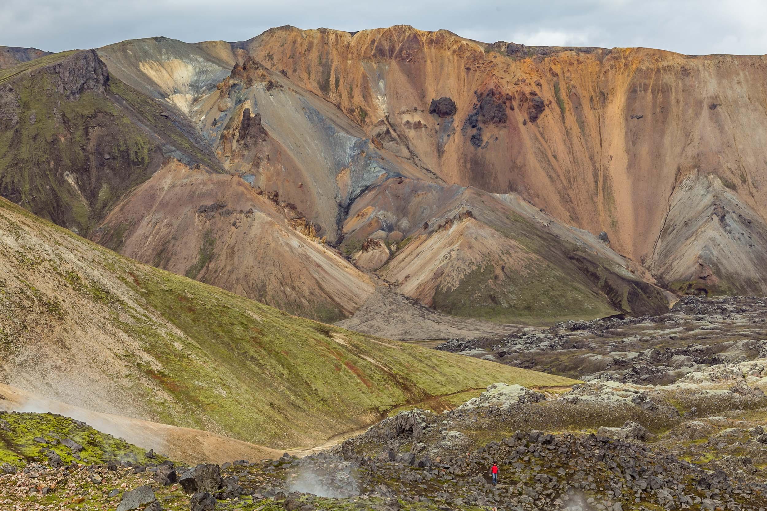 Hiker traversing lava flows in Landmannalaugar