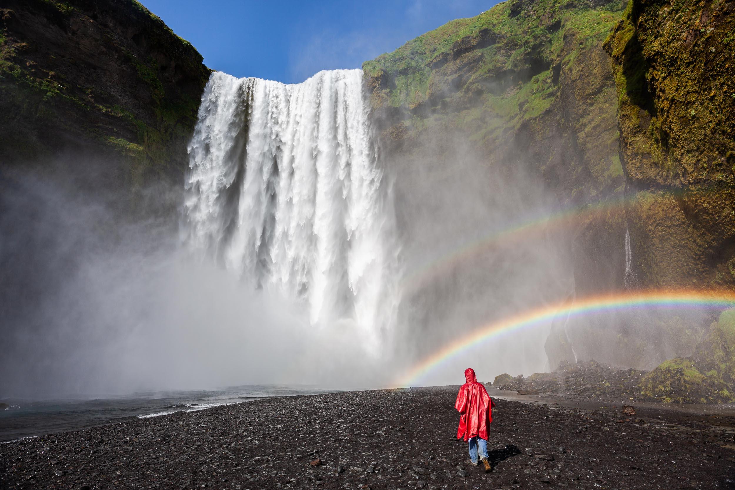 Skogarfoss waterfall with red raincoat under a rainbow