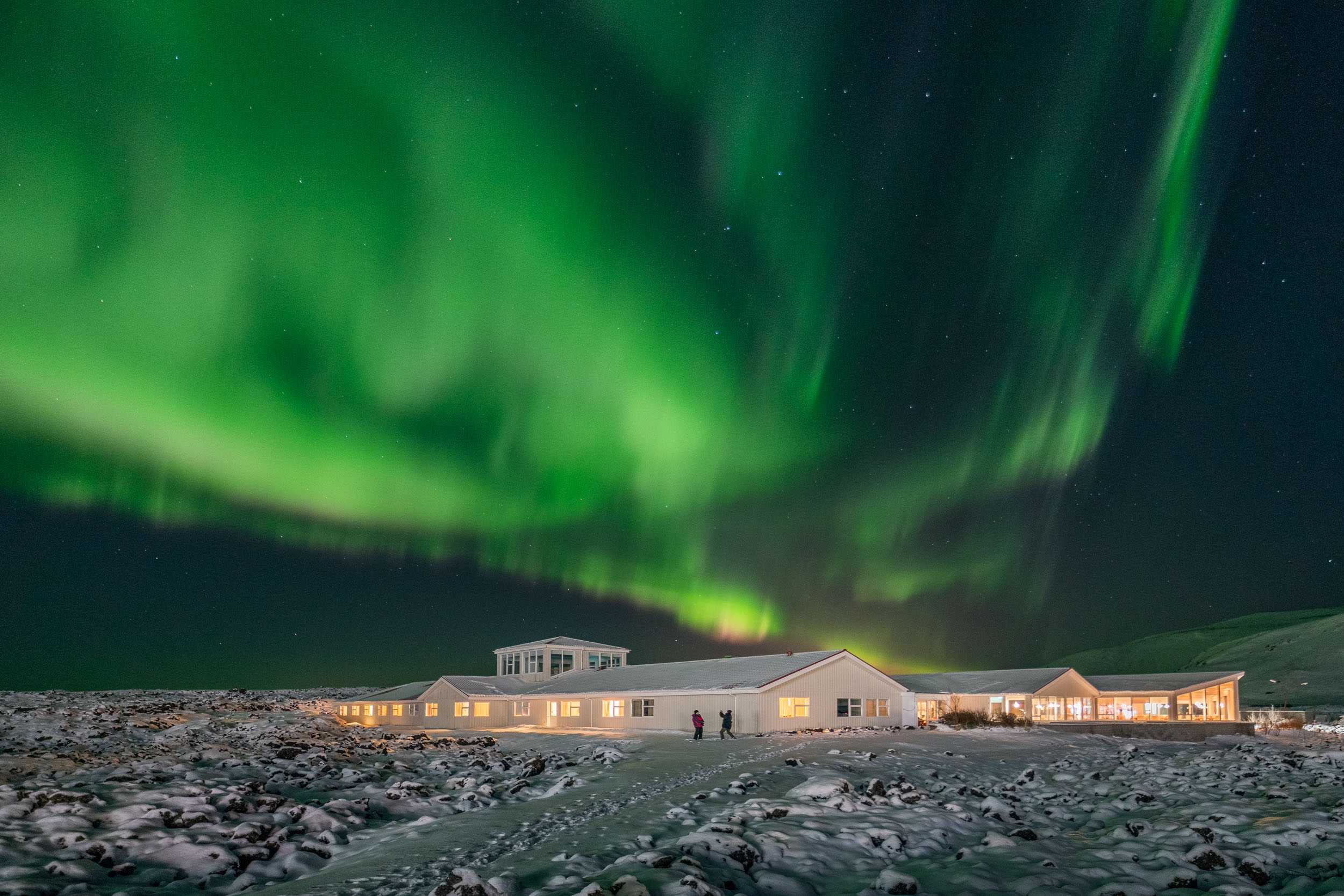 Aurora Borealis dancing above Northern Light Inn, Iceland .