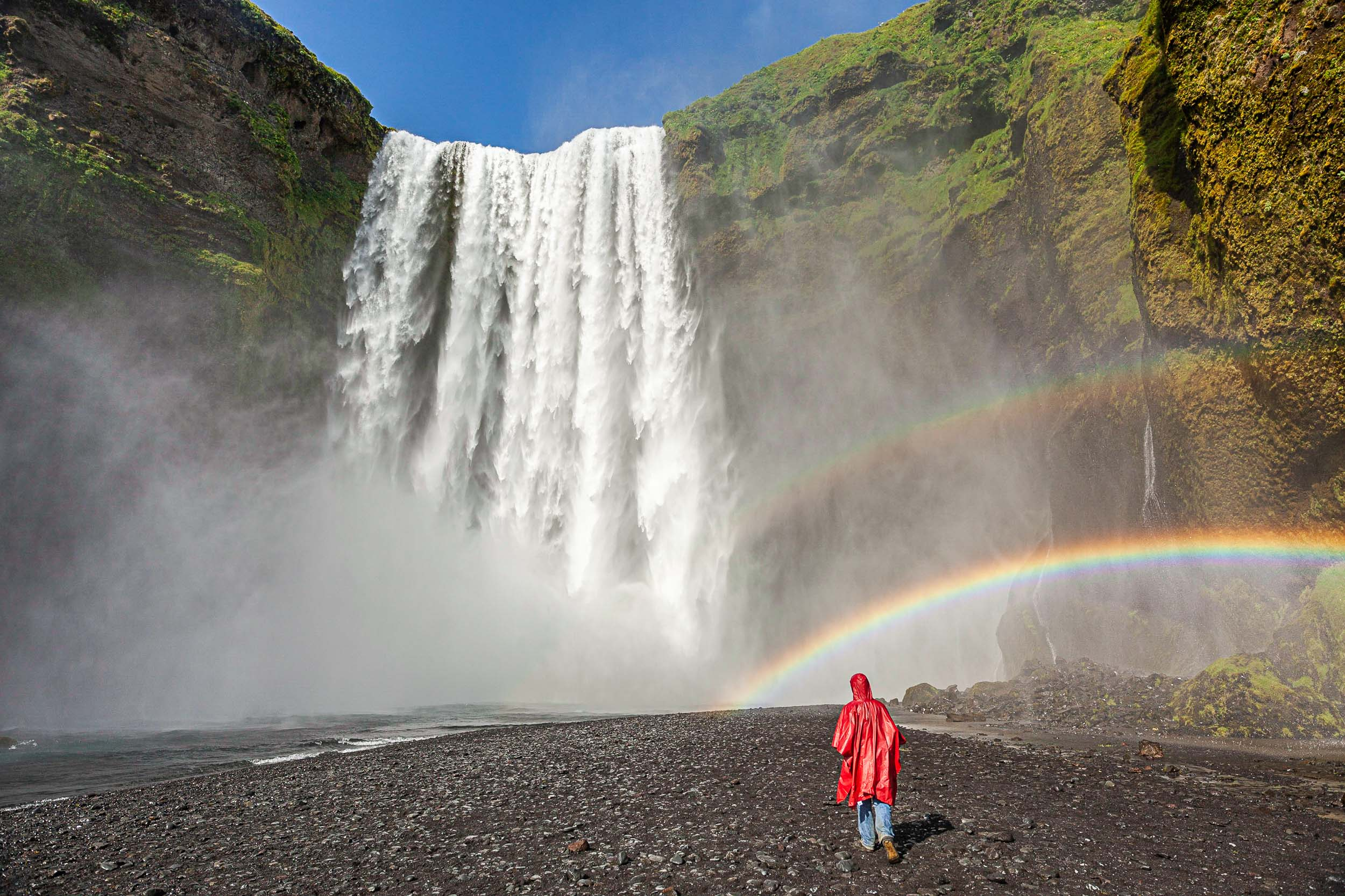 Skogarfoss waterfall with red raincoat under a rainbow