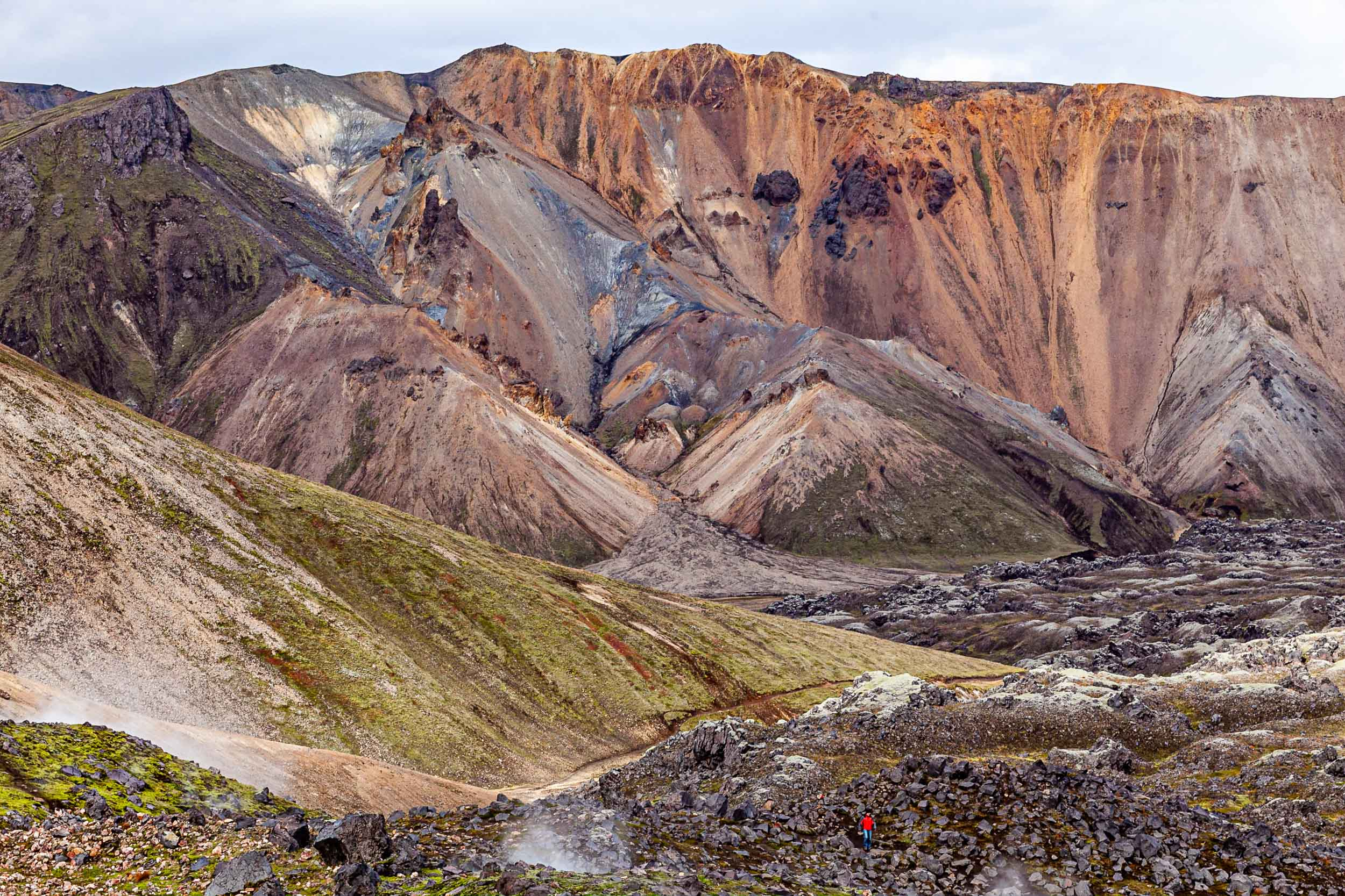 Hiker traversing lava flows in Landmannalaugar