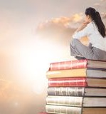 businesswoman-sitting-books-stacked-sun-clouds-digital-composite-89400068.jpg