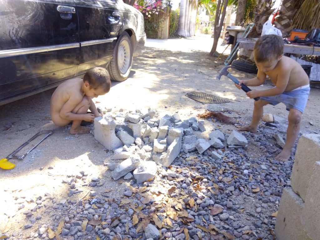 child playing with block and making pretend cement