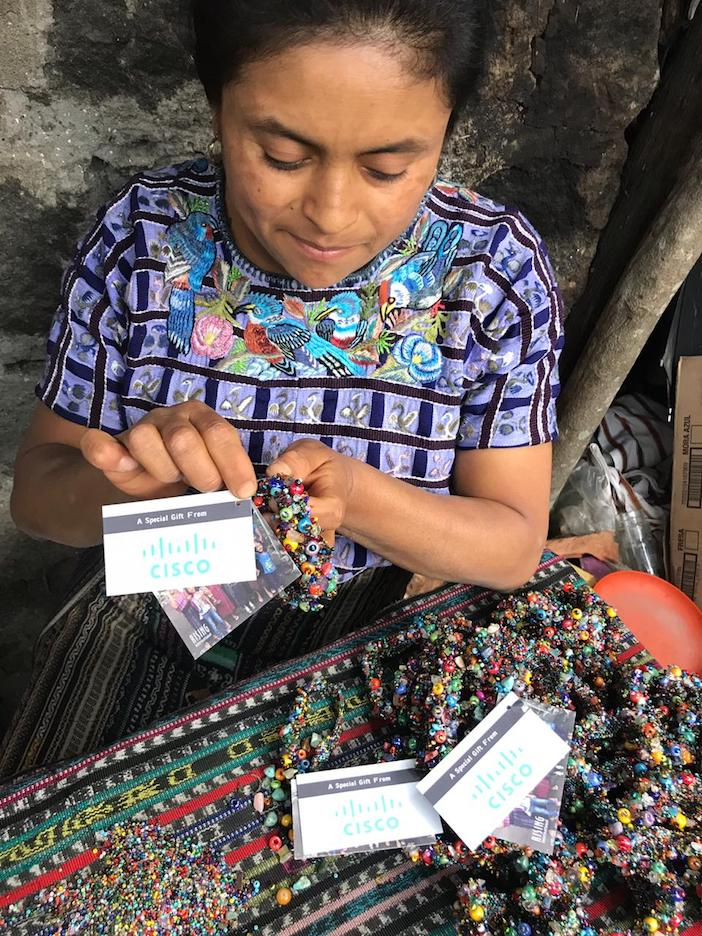 A woman in Guatemala creating handmade bracelets for Cisco.