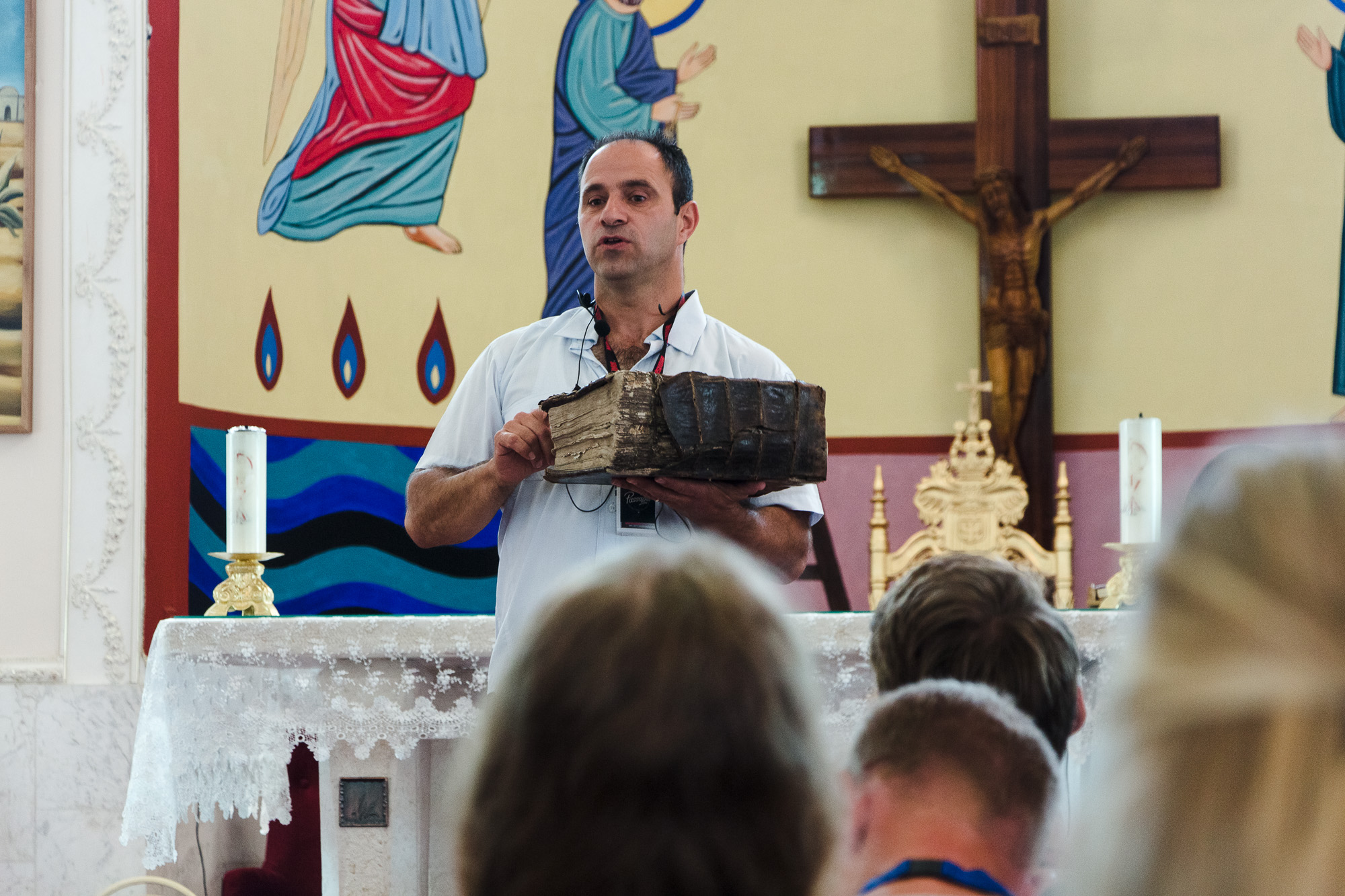 Shadi Khalloul presents an ancient Aramean Bible while speaking to a group of students at the Syriac Maronite Church of Antioch in Jish.