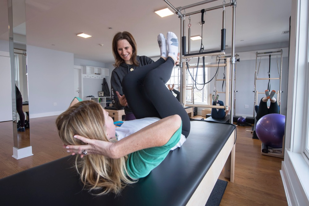 Philosofit Pilates Instructor Susan Moran Sheehy works with a member during a Pilates session in their East Hampton studio on Friday, 3/9/18