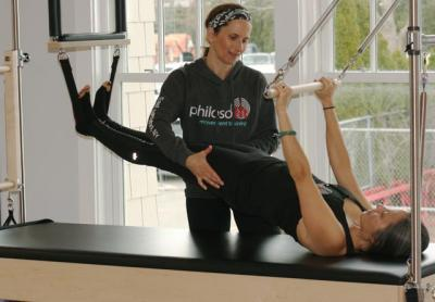 """Overseen by Susan Moran Sheehy, Marie Weller arched into the breathing exercise on a Pilates """"Cadillac"""" apparatus at Philosofit Saturday afternoon. Photo by Jack Graves."""