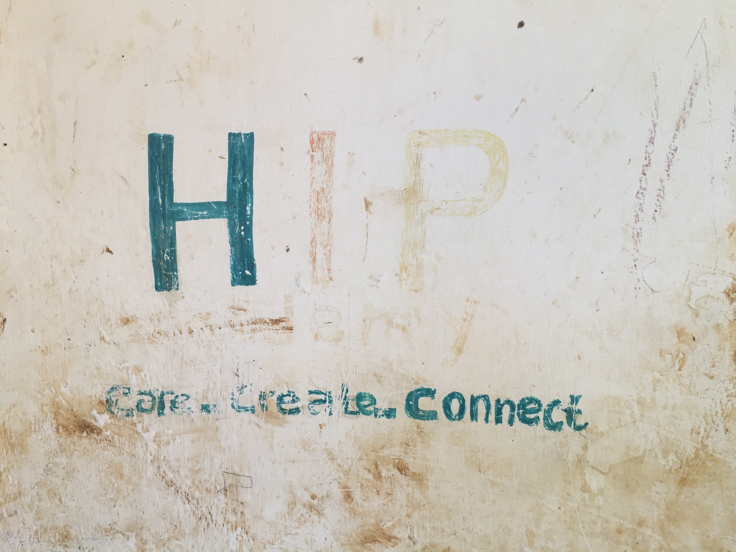 "On one of the outside walls of the school was this painted sign with ""HIP"" written on it as well as a school motto: ""Care. Create. Connect"". Both were starting to fade from time and weather."