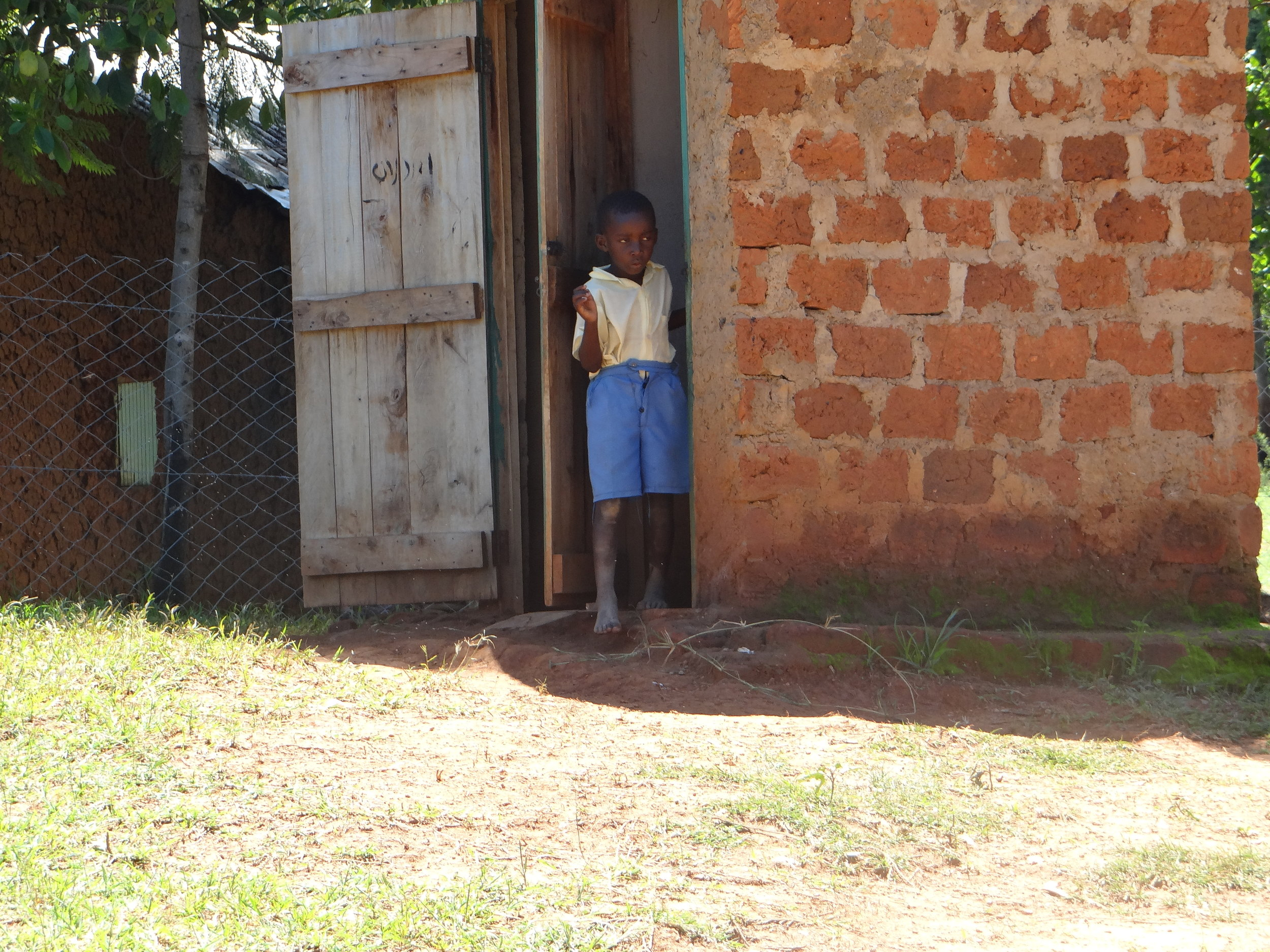 One of HIP's students coming out of the latrine. This boy did not have a pair of shoes for school.
