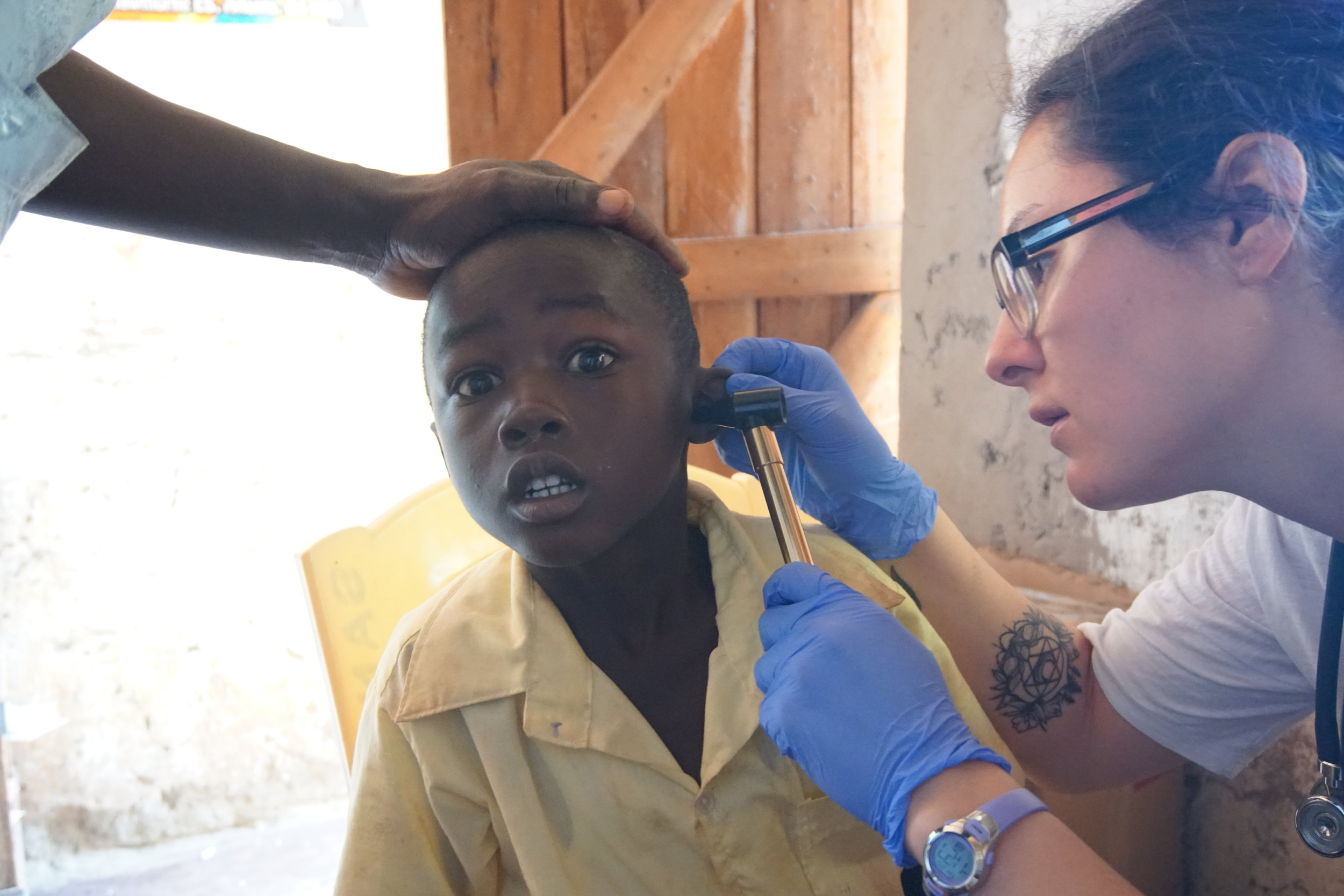 Brooke checks the ears of one of HIP's students. The otoscope was cold and the student wasn't sure what to make of it being in his ear.