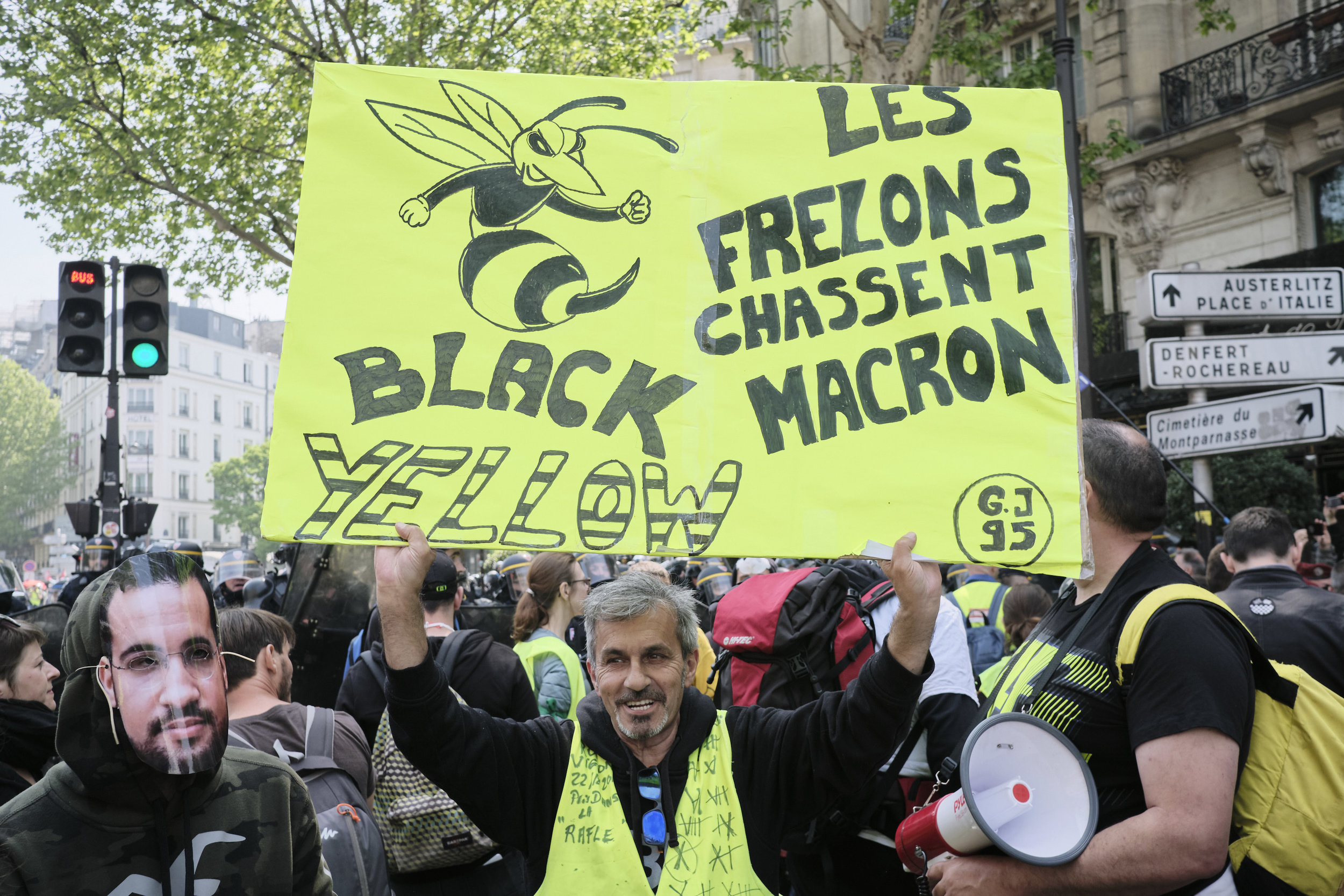 """Yellow vest participant of the  protest a poster """"The Hornets Hunt Macron."""""""