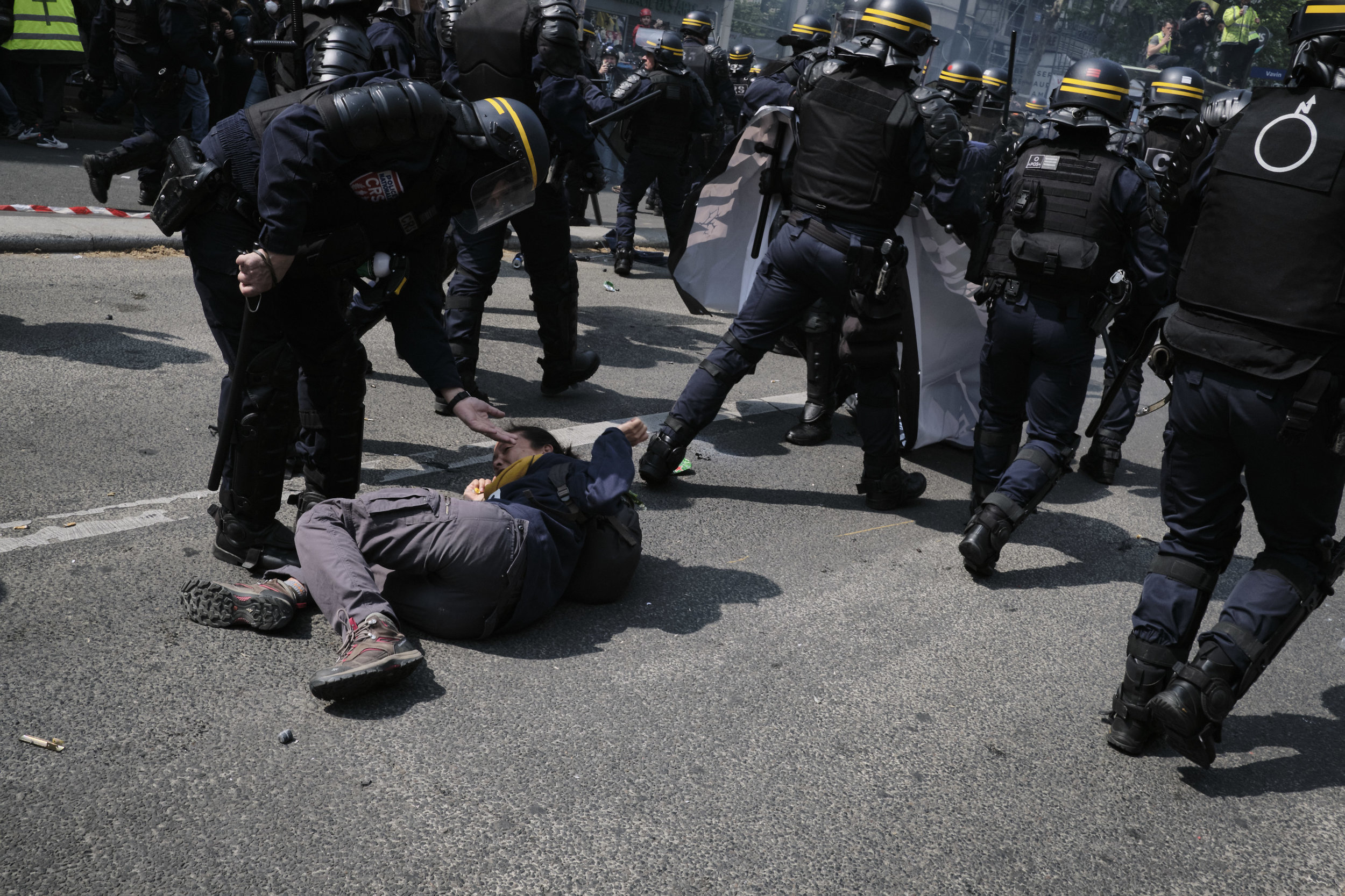 Officer helping a protest participant up after she has been knocked down by the police during an attempt to control the crow.