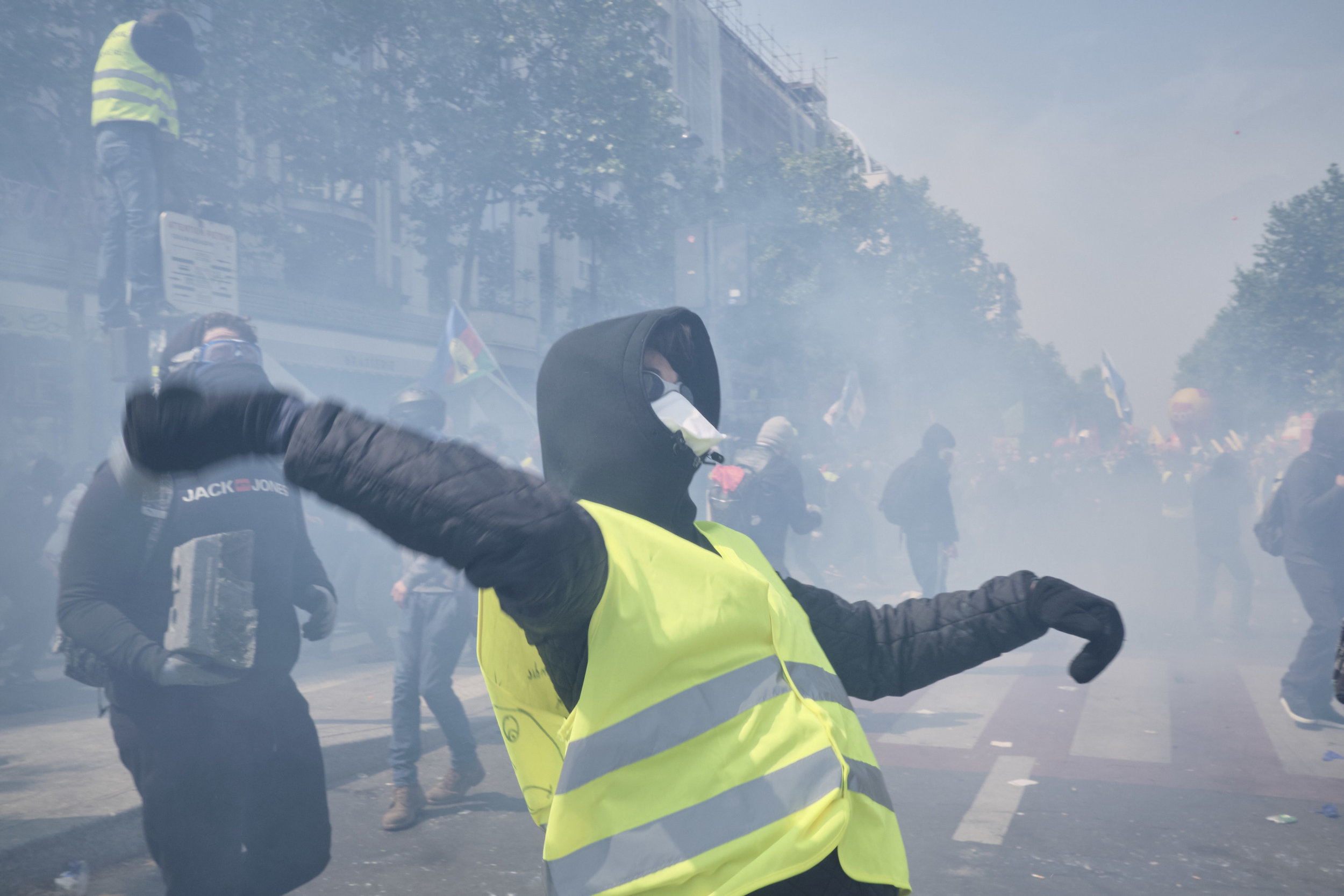 Yellow vest protester throwing a tear gas grenade back at the police during a confrontation at Boulevard du Montparnasse.