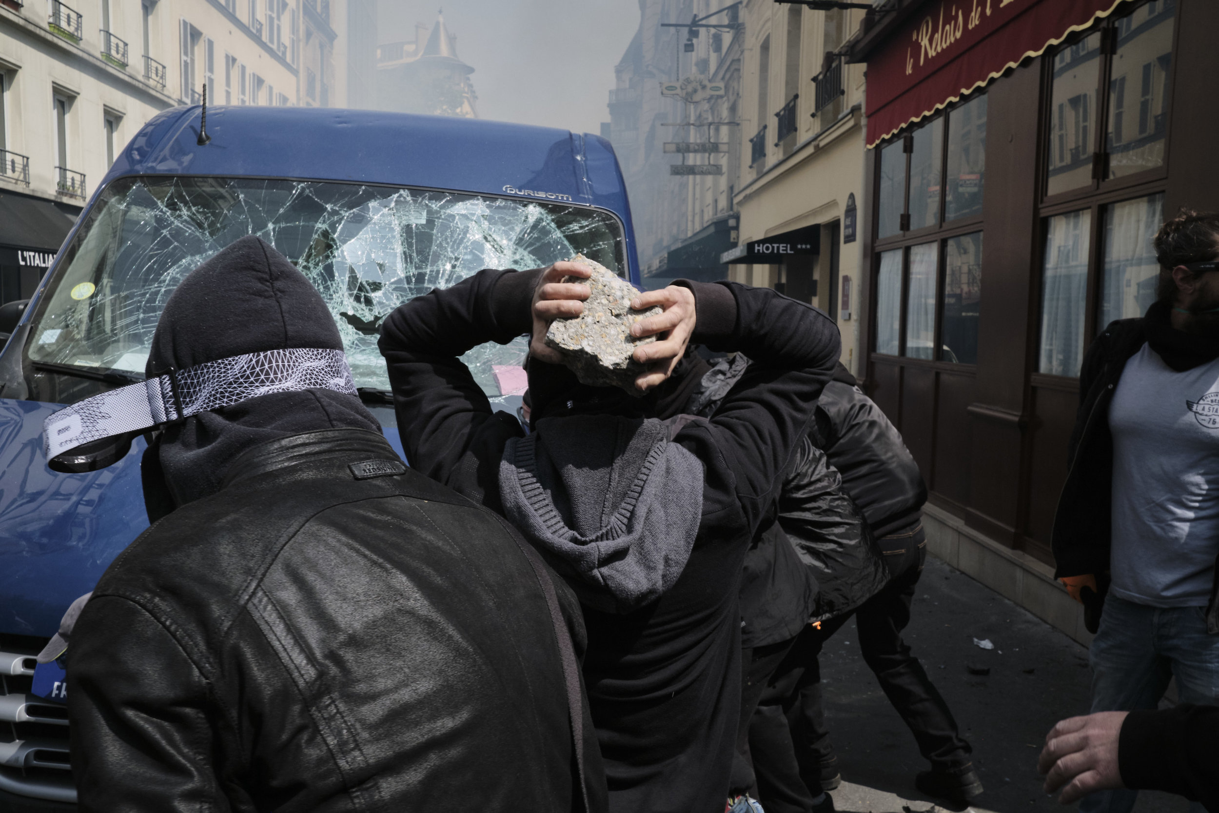 Anti-fascist participants of the protests are destroying a parked van after pushing back the police to the Rui Vavin.