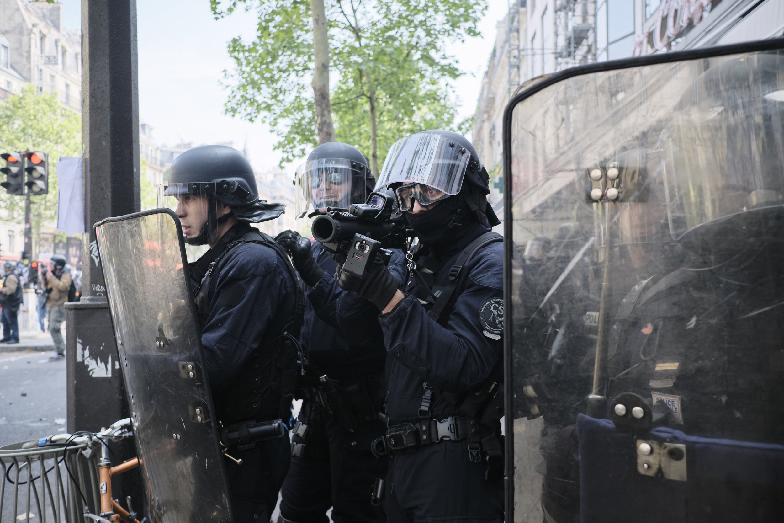 """Police officer aiming  LBD40 """"non lethal"""" weapon at the crowd of protesters."""