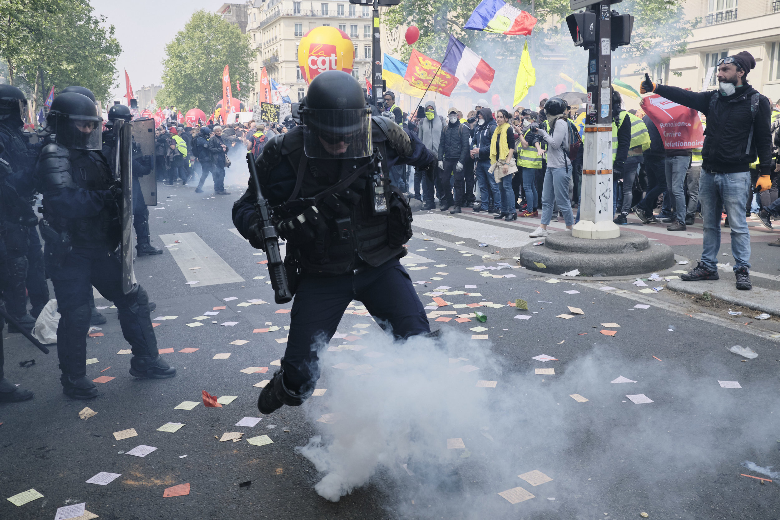 Police officer kicking a tear gas grenade back at the crowd of protesters at Boulevard du Montparnasse after it has been thrown back at them shortly after an attempt to control the crowd.