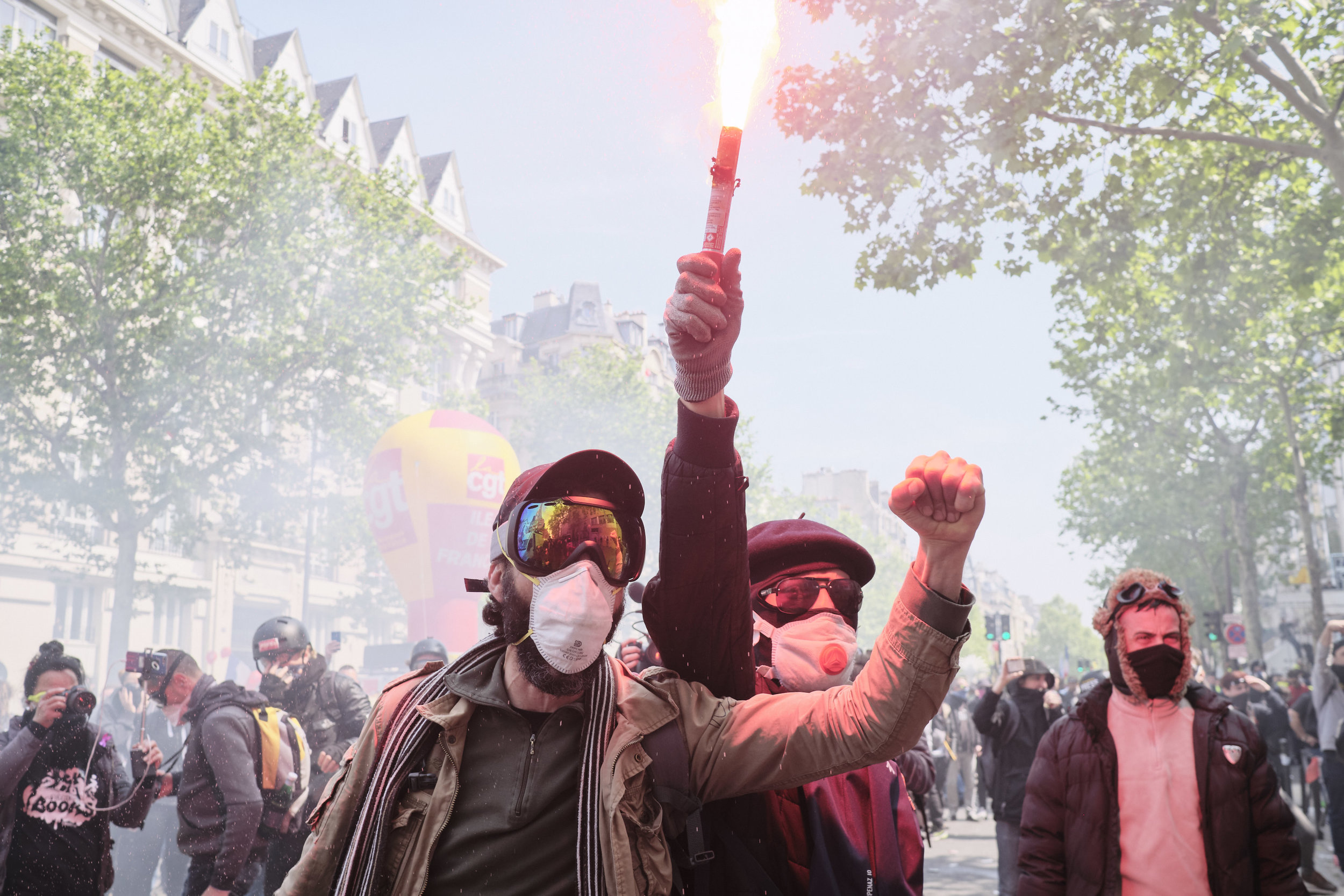 Protest participants celebrating with light flairs after successfully withstanding a crowd control manoeuvre by the police at Boulevard du Montparnasse.