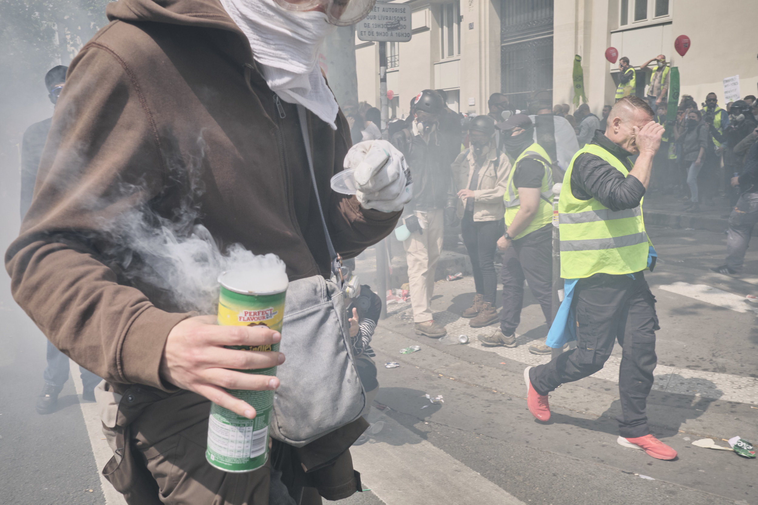 """Protest participant collecting tear gas grenades and storing them in a """"Pringles"""" container during the police attempt to control the crowd at Boulevard du Montparnasse."""