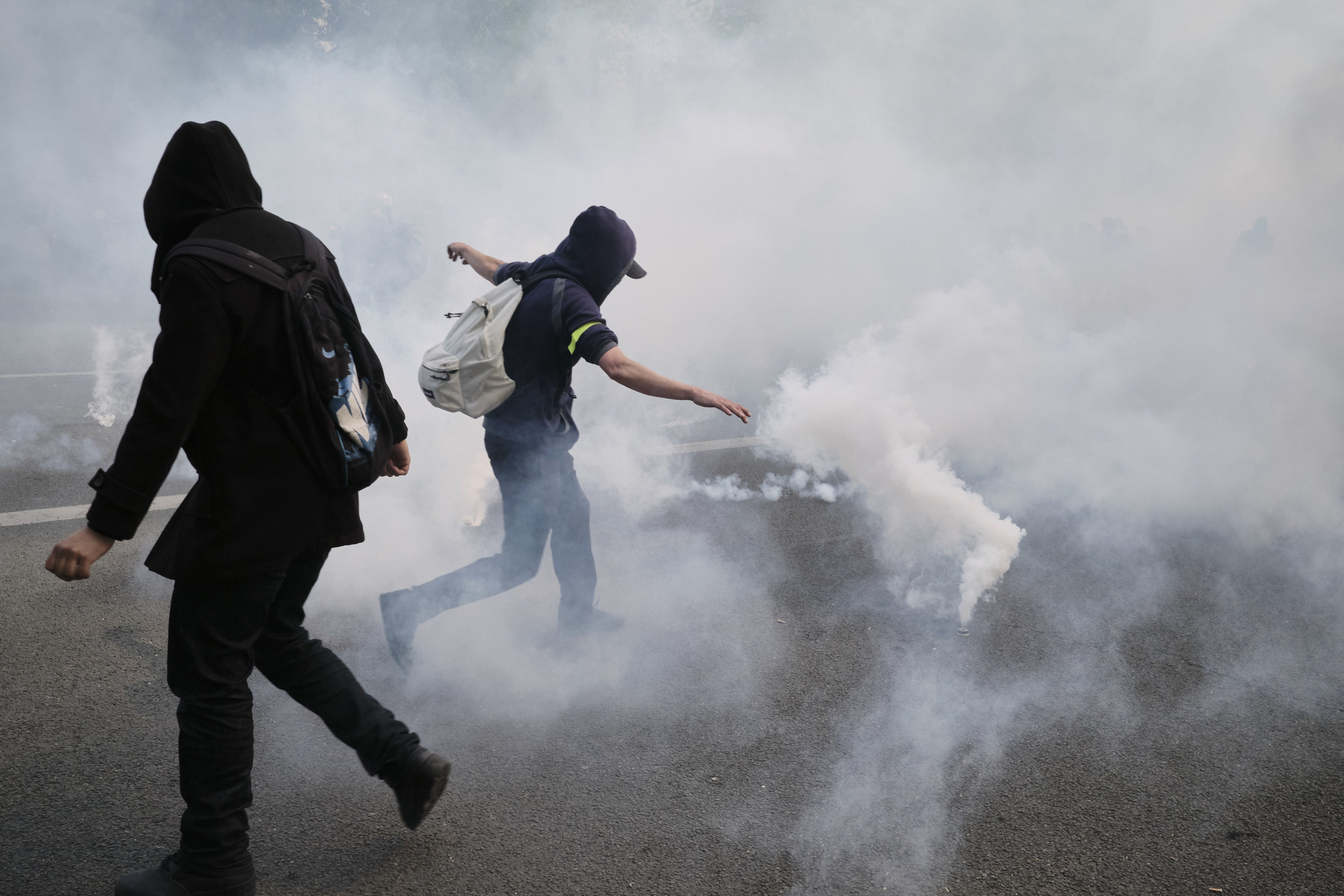 Protesters kicking tear gas grenades away from the crowd of protesters towards the police during a confrontation.