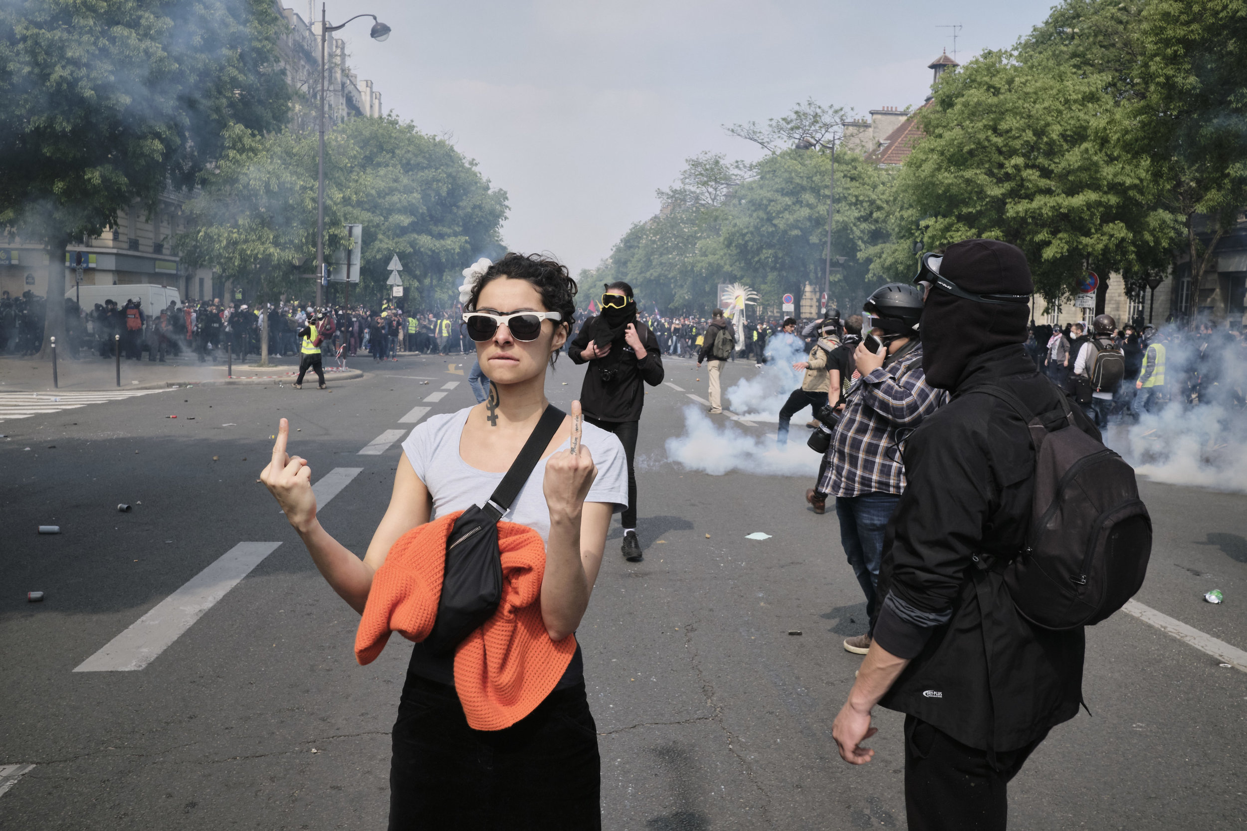 Angry protest participant showing the middle finger to the police after an attempt to control the crowd by using tear gas during the march to The Palace D'italie.