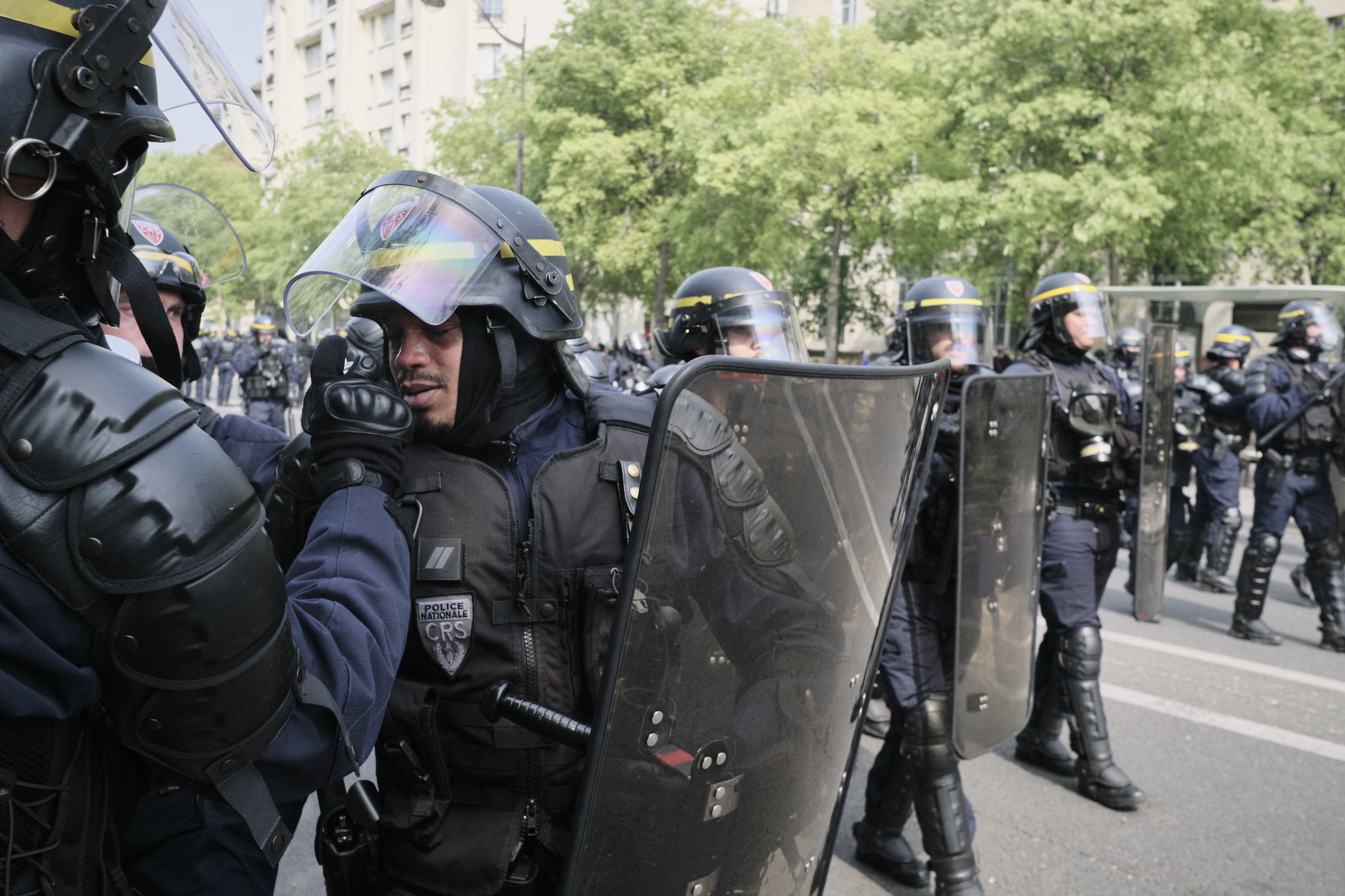 Police officer cleans his colleagues eyes from tear gas after a confrontation between the police and protesters in an attempt to control the crowd during the march to The Place D'italie.