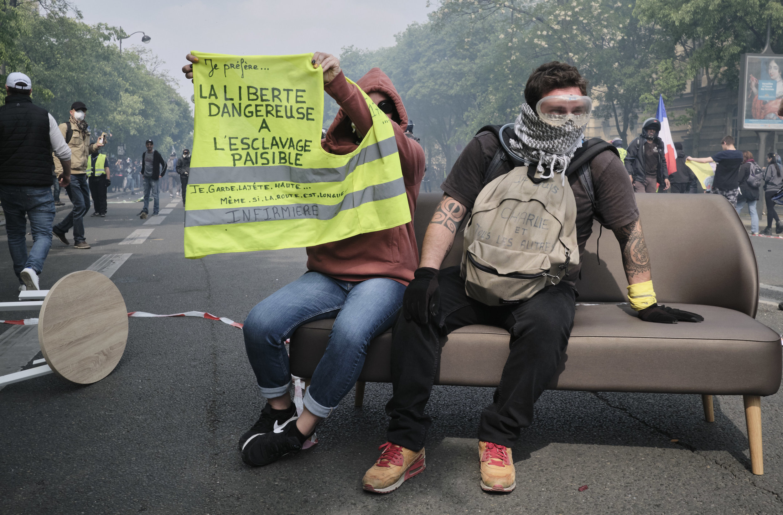 """Yellow vest protest participants holding a vest. """"I prefer dangerous freedom to peaceful slavery"""". After a confrontation with the police and an unsuccessful attempt to control the crowds by using tear gas, during the march towards The Place D'italie."""
