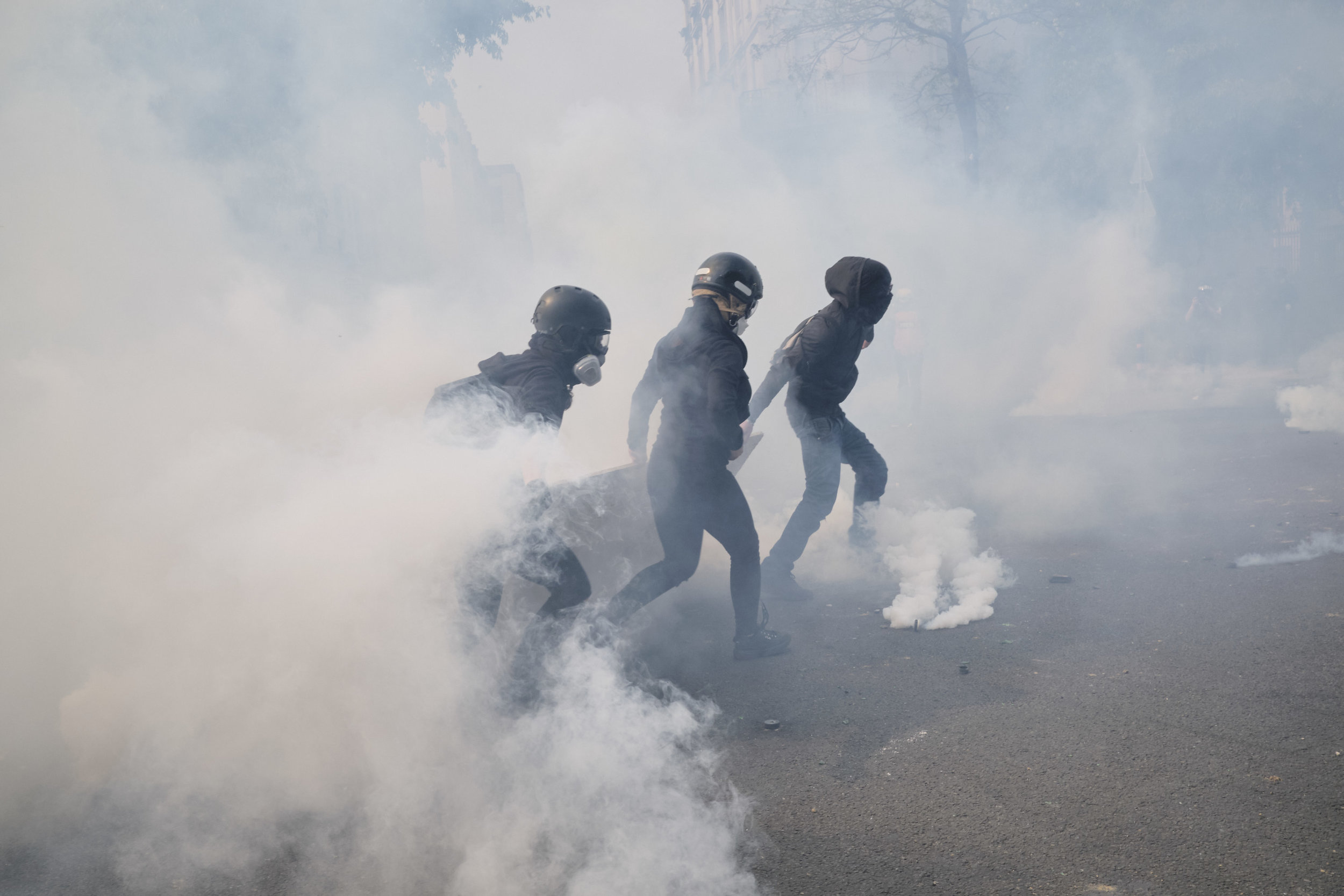 Protest participants trying to get away from the tear gas fired by the police in attempt to control the crowds during the march towards The Palace D'italie.