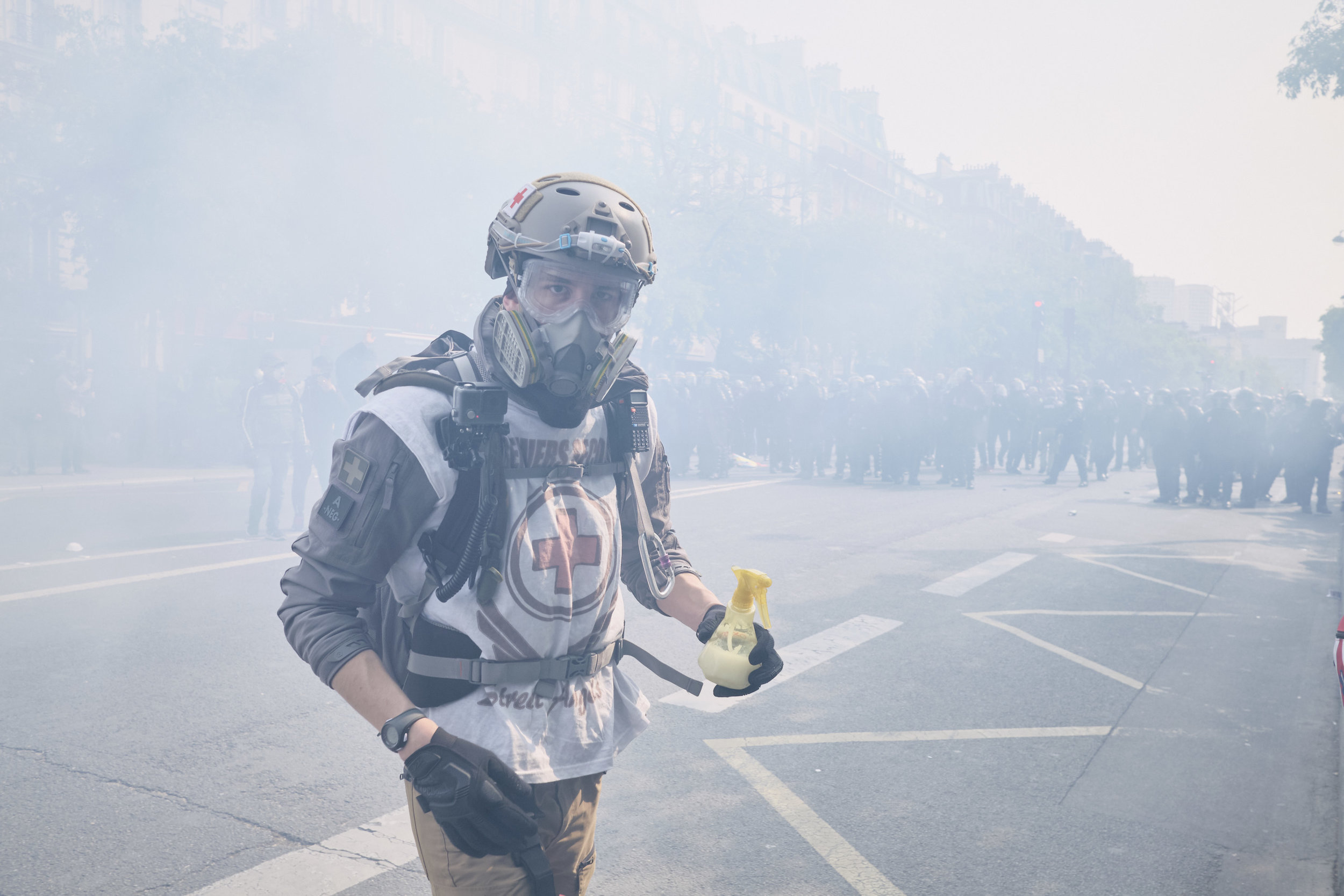 Civilian street medic on his way to help an injured protest participant right after an attempt by the police to control the crowd using tear gas at The Avenue des Gobelins.
