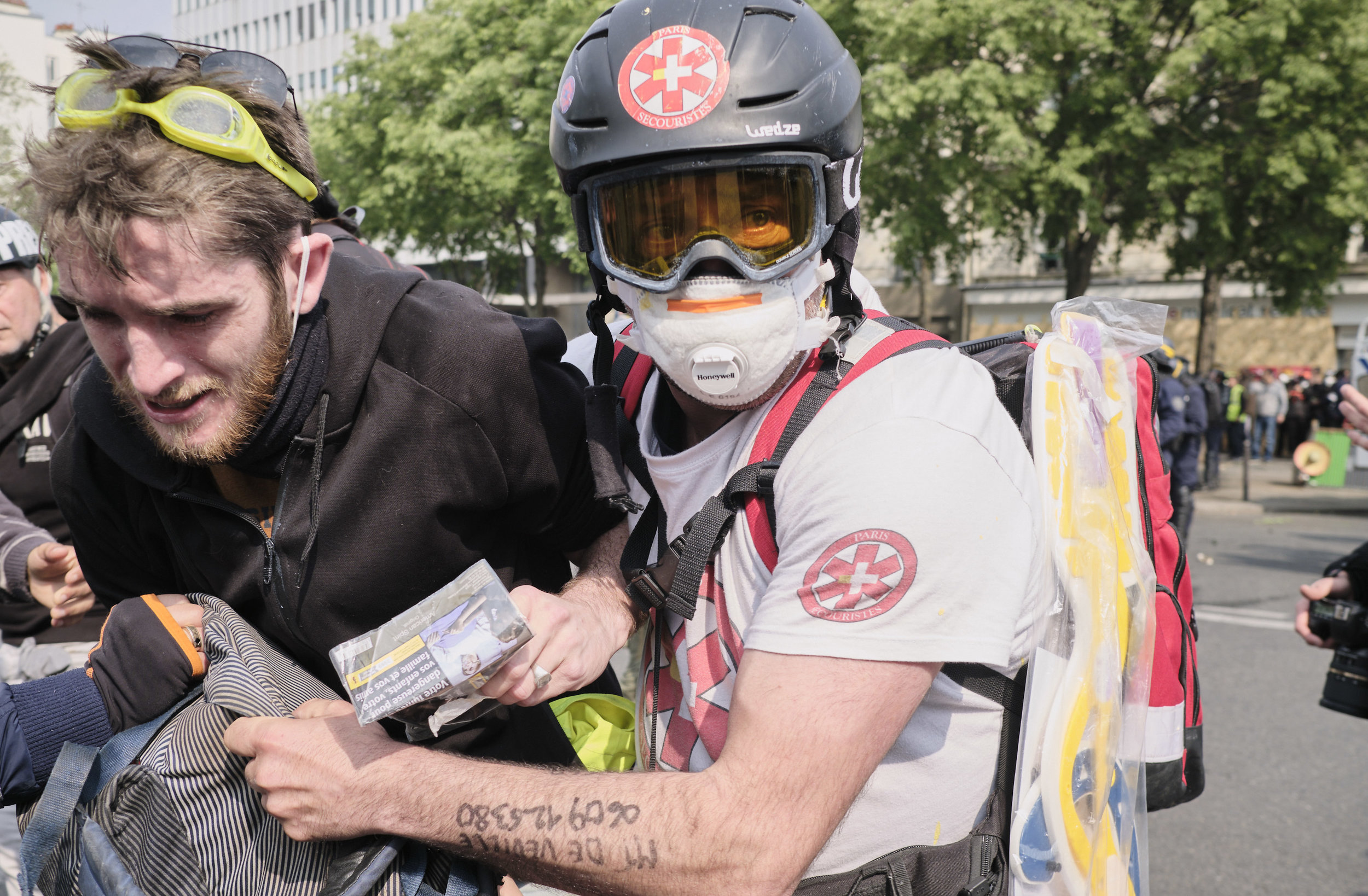 Civilian street medic taking an injured protest participant to safety during an attempt by the police to control the crowd using tear gas at The Avenue des Gobelins.