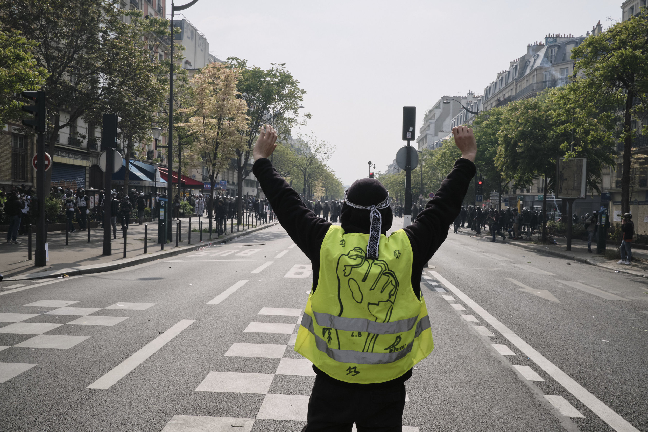 Yellow vest participant standing in front of police at The Boulevard Argo during the march to The Place D'italie.