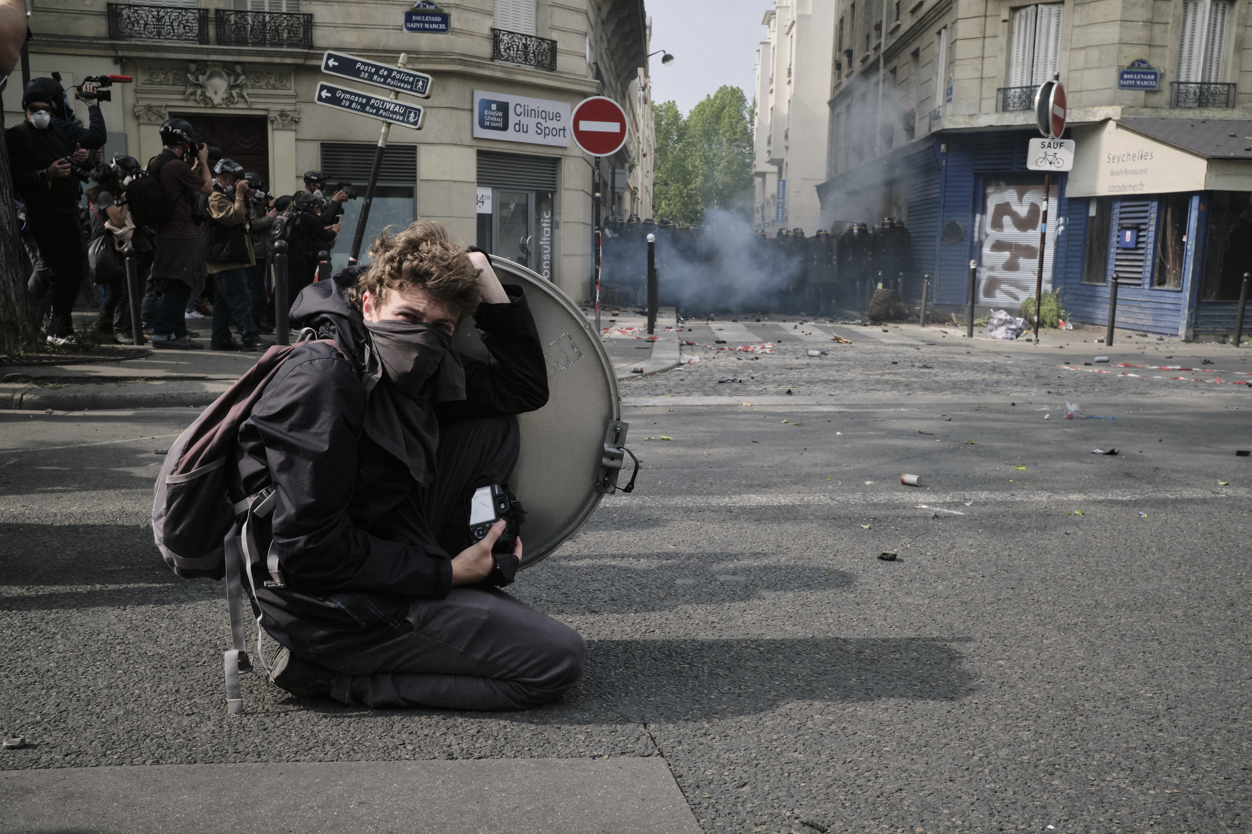 Participant photographer hiding behind a road sign during a violent confrontation between the protesters and the police at The Boulevard Arago.