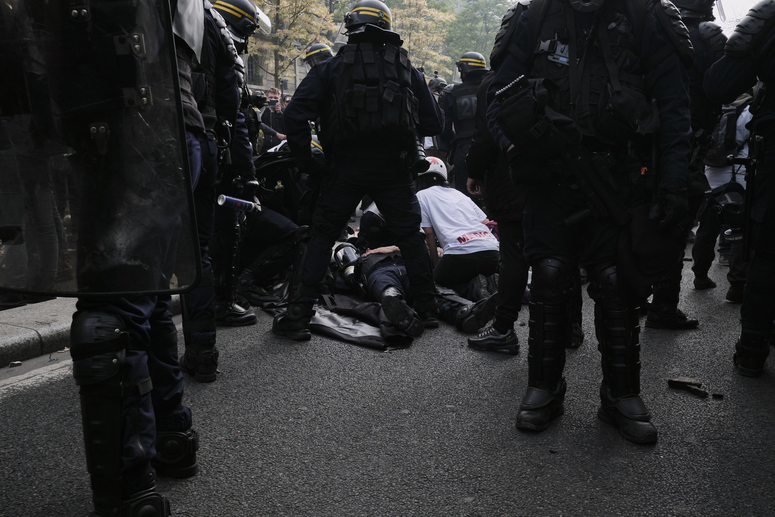 Civilian street medic helping an injured police officer who was injured during a confrontation with the protesters at The Boulevard Arago.