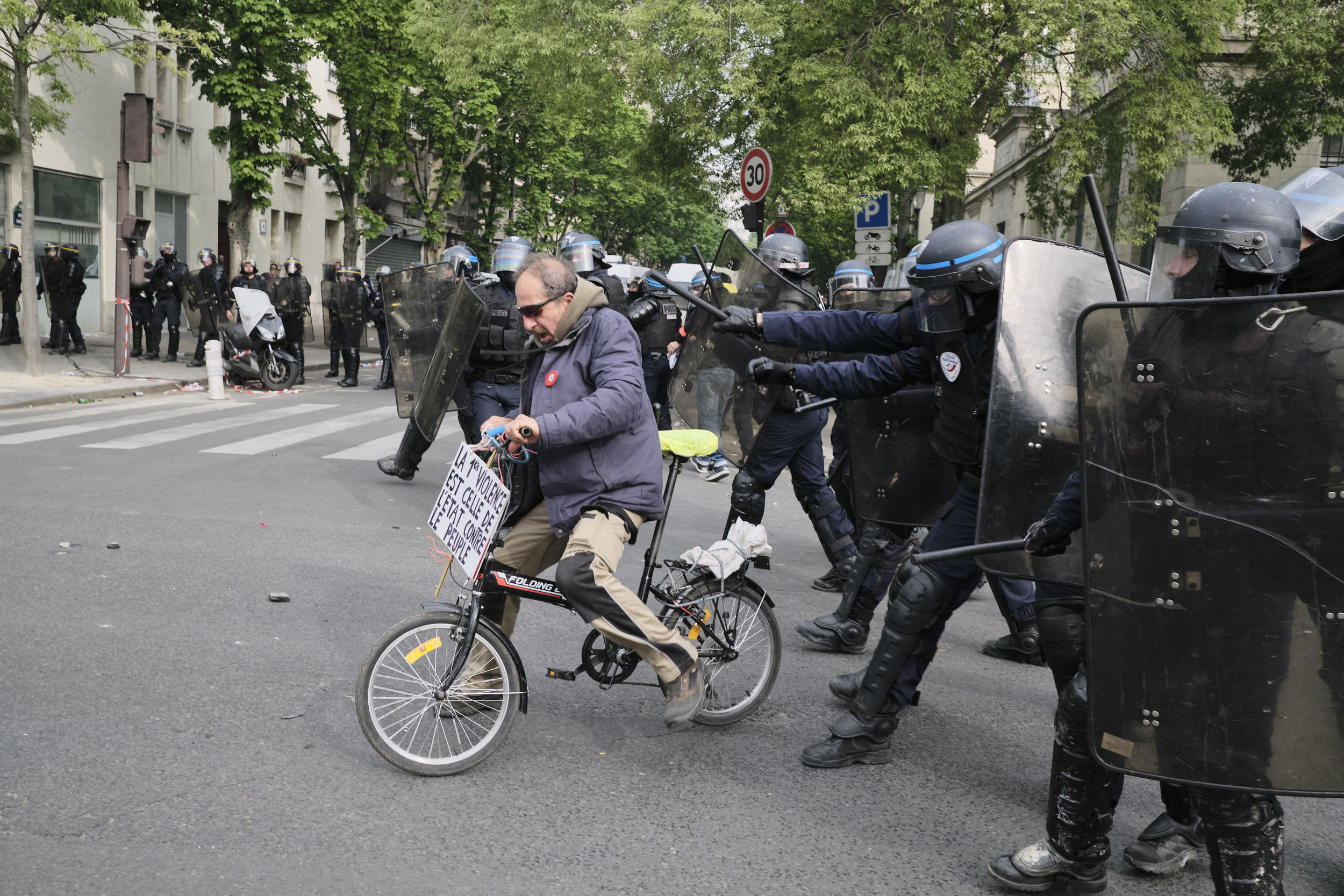 Riot police pushing the protest participant away during a crowd control manoeuvre at The Avenue des Gebelins.