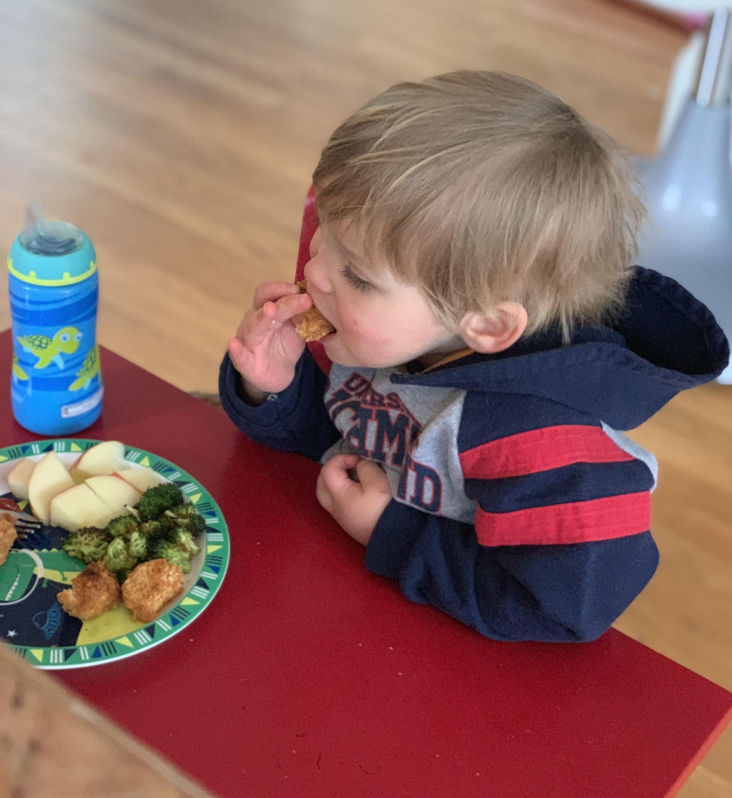 Joseph eating homemade chicken nuggets. I wouldn't buy the plastic plate and cup now, but I definitely won't be throwing them away to add to a landfill.