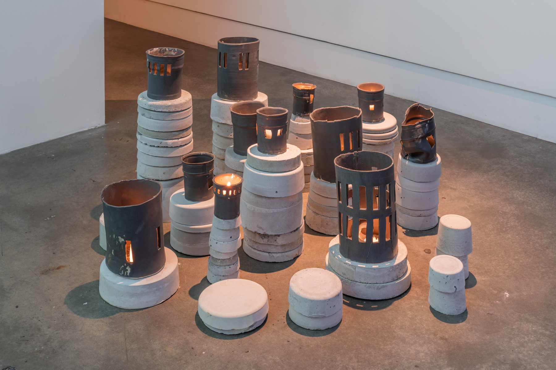 Untitled (Towers), suite of 12 with cement pillars , 2019  Porcelain, Stoneware, Cement  The ceramic and cement towers (lanterns) draw on the history of institutional architecture, industrialized violence, and youth carceral geographies to think through growth and development. The lanterns are fashioned in panopticon shapes that echo a design common to U.S. prison architecture, and display the shape of the stark windows of the youth detention center that Paz documented in the adjacent film. As a whole, they reflect the occlusion and refracting of light to this controlled environment.   The ceramic portions of each are held atop cement pillars mixed from a northwest cement company regularly employed to construct regional schools, universities, and penal structures.
