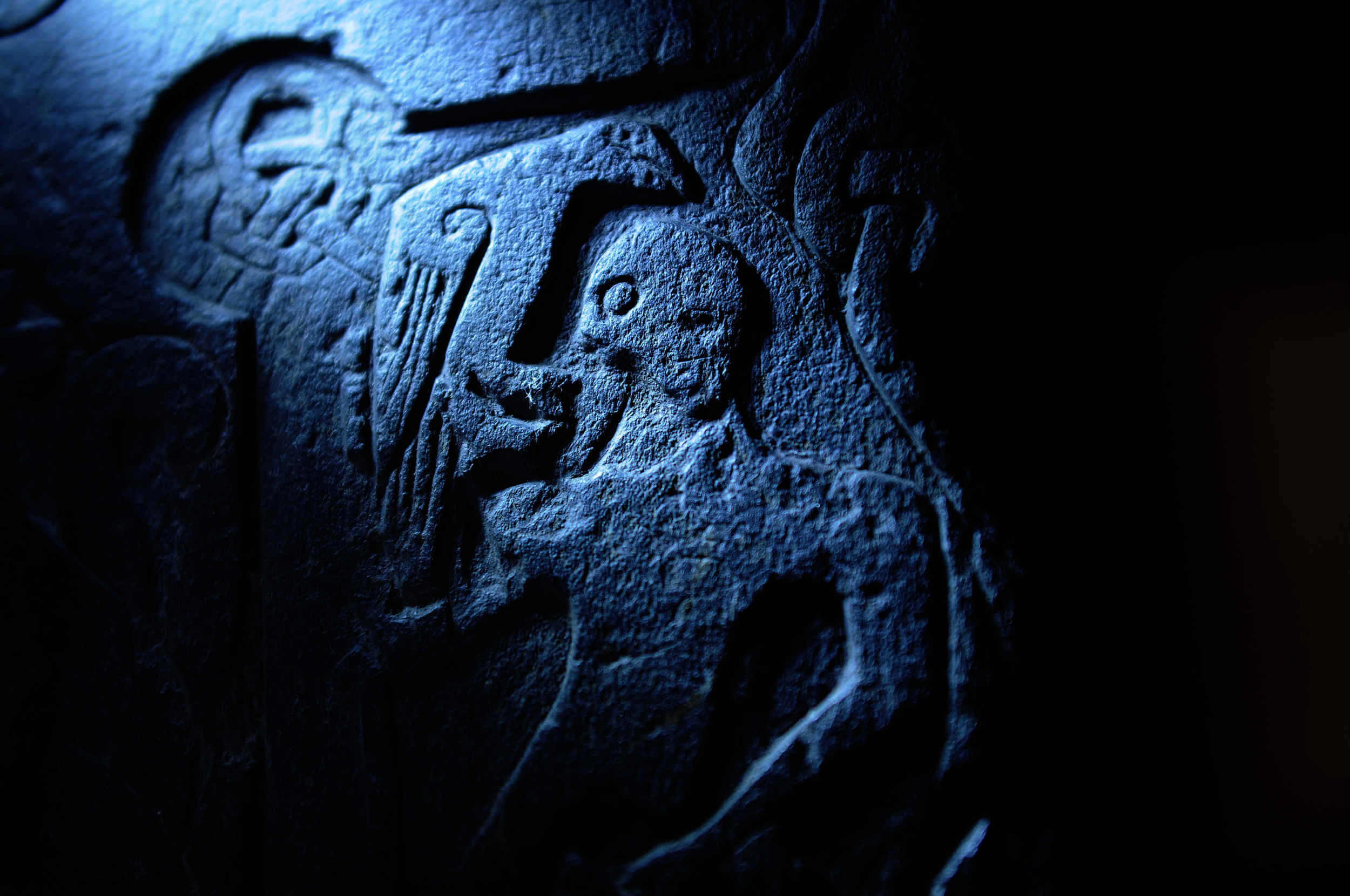 Ragnarok, as depicted on Thorwald's Cross, featuring Norse god Odin and his raven. The stone was carved around 940AD and the surviving fragment resides at Kirk Andreas church.