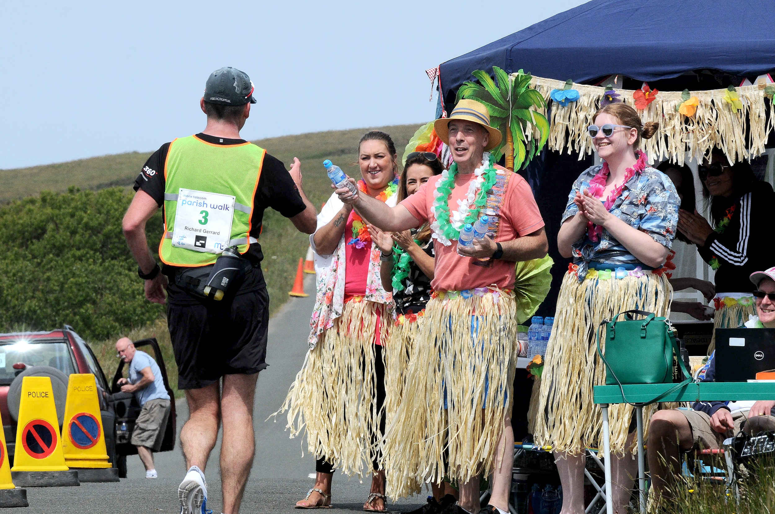 Race walker Richard Gerrard accepts a drink from the staff of First Names Group, who created an 'Oasis' at Eary Cushlin to support competitors in the Parish Walk