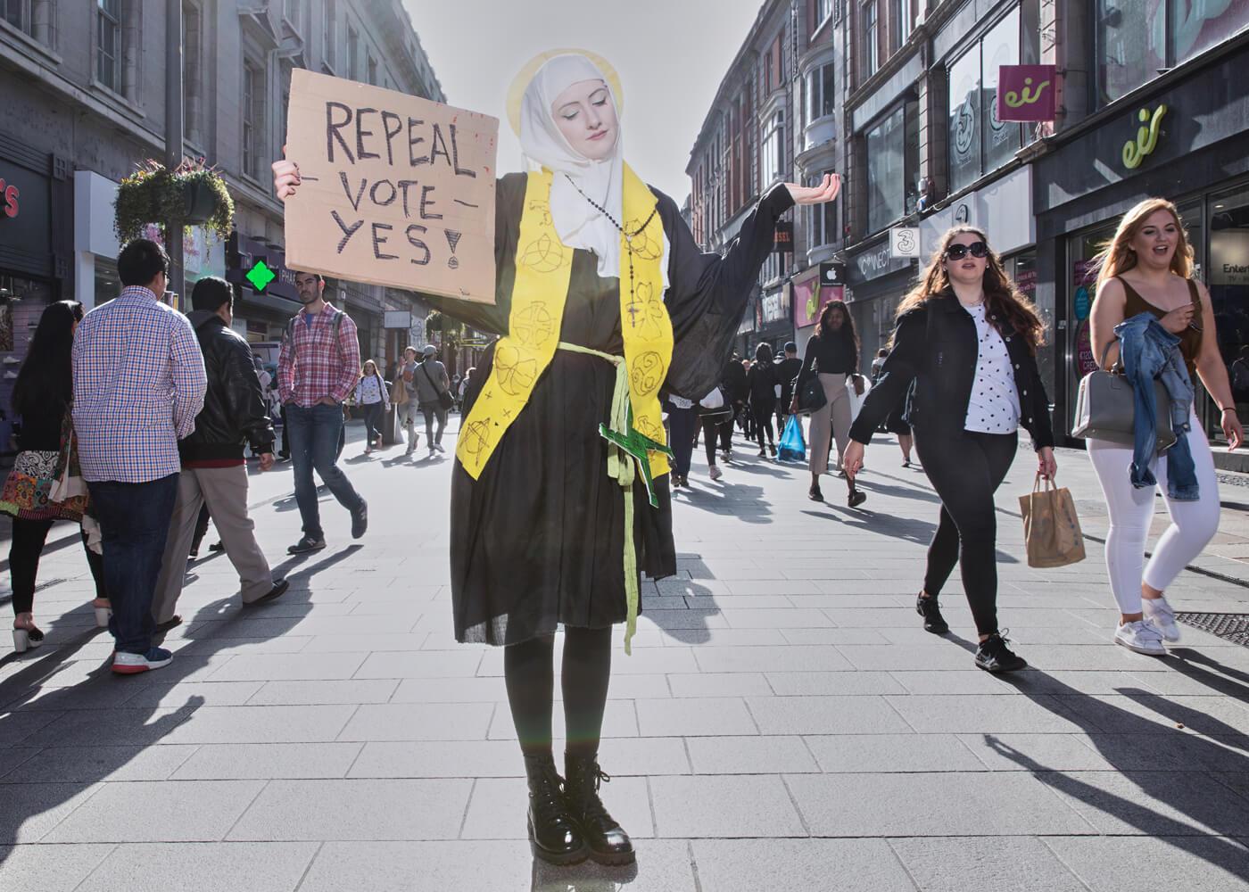 Saint Brigid, Dublin.  Repeal campaigner Megan Scott dressed as Saint Brigid, Ireland's female patron saint, on Dublin's main shopping street. Saint Brigid's miracle was to cause pregnancy to vanish. It is thought modern Catholic scholars suppressed this part of Saint Brigid's story.