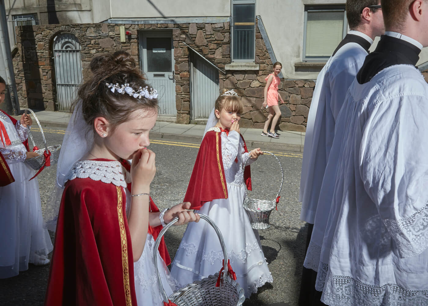 Brides of Christ, Cork.  Eight year old girls dressed as 'Brides of Christ' kiss rose petals that represent Christ's blood before scattering them on the floor. First communion is still a rite-of-passage for girls in Ireland.